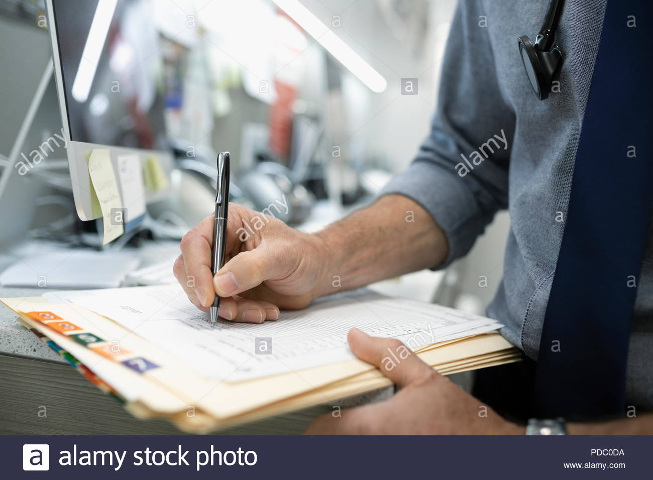 Close up male doctor writing in medical record - Stock Image