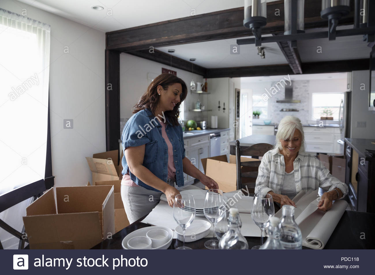 Daughter helping senior mother downsize, packing dishes - Stock Image