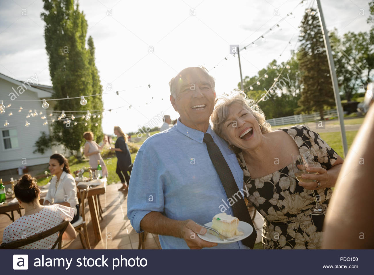 Happy couple celebrating anniversary, eating cake at garden party - Stock Image