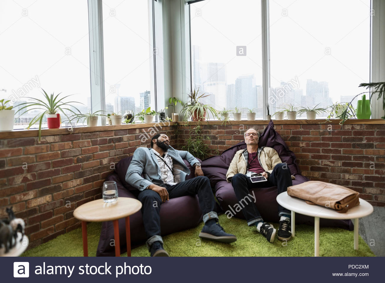 Creative businessmen napping on beanbags in office - Stock Image
