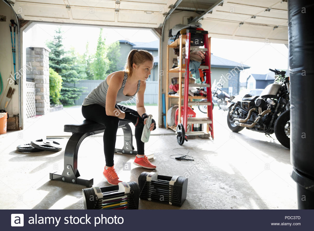 Young woman weightlifting, resting in garage - Stock Image