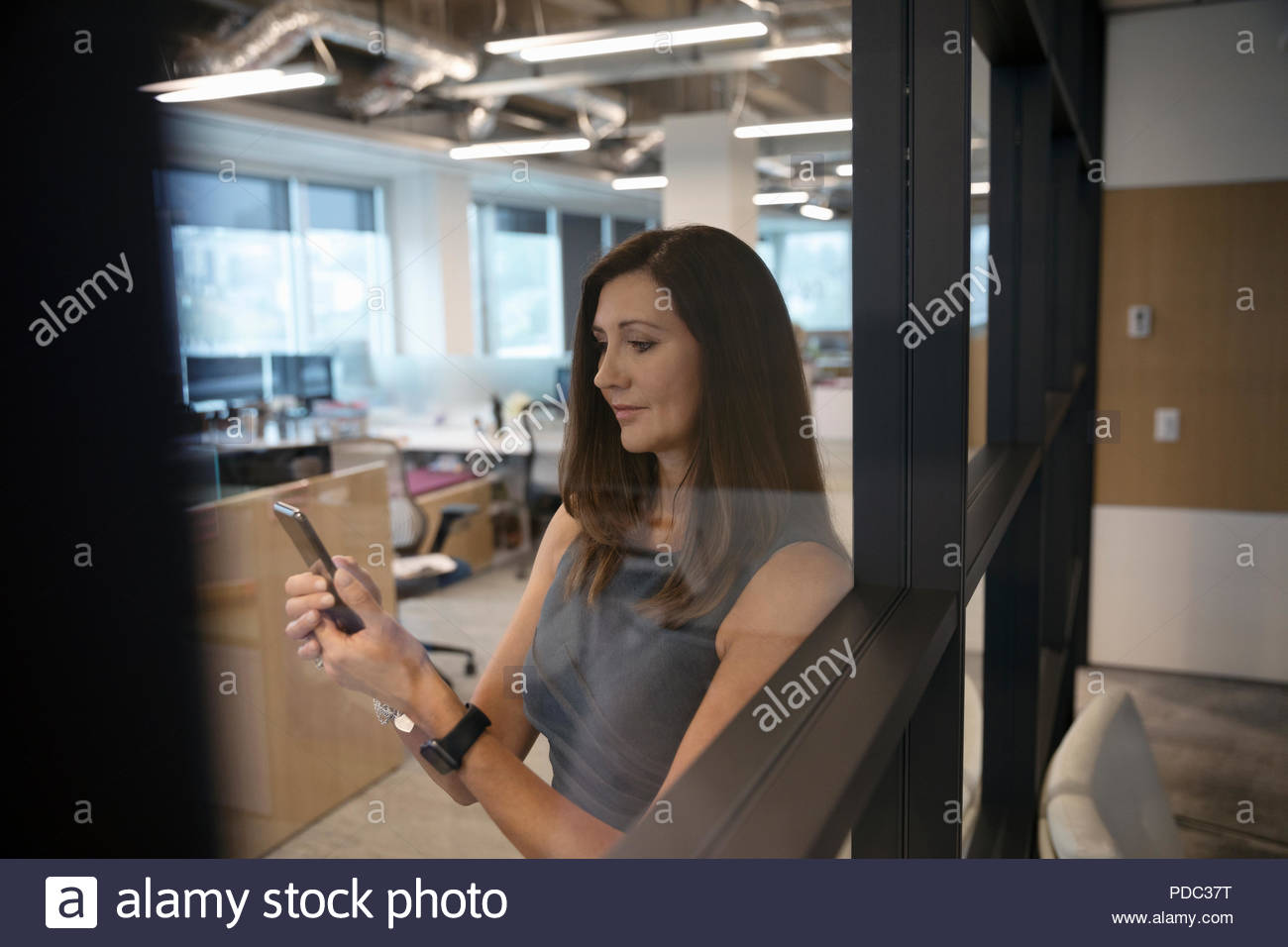 Businesswoman using smart phone in office - Stock Image