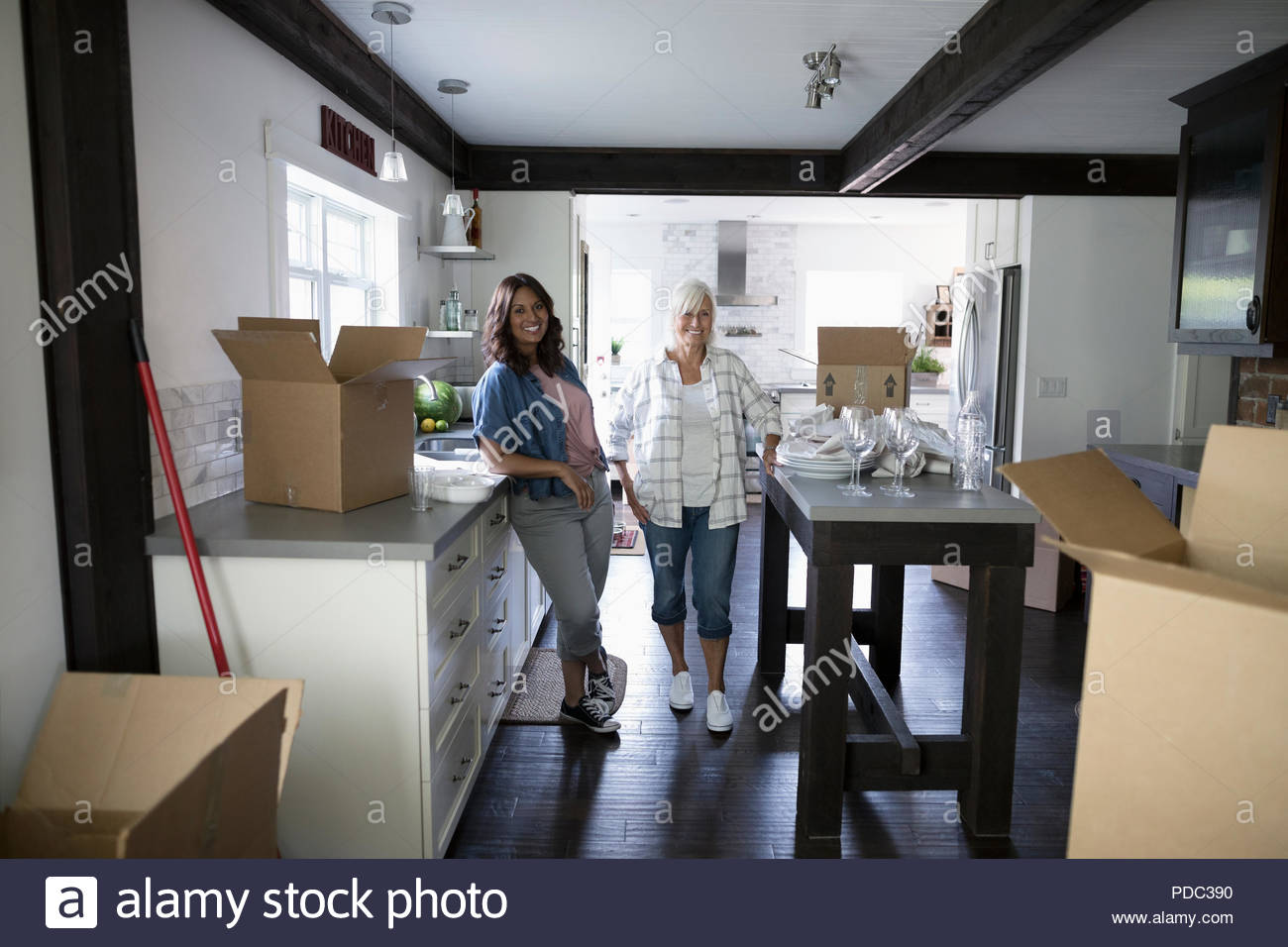 Portrait smiling daughter and senior mother, downsizing and packing kitchen - Stock Image