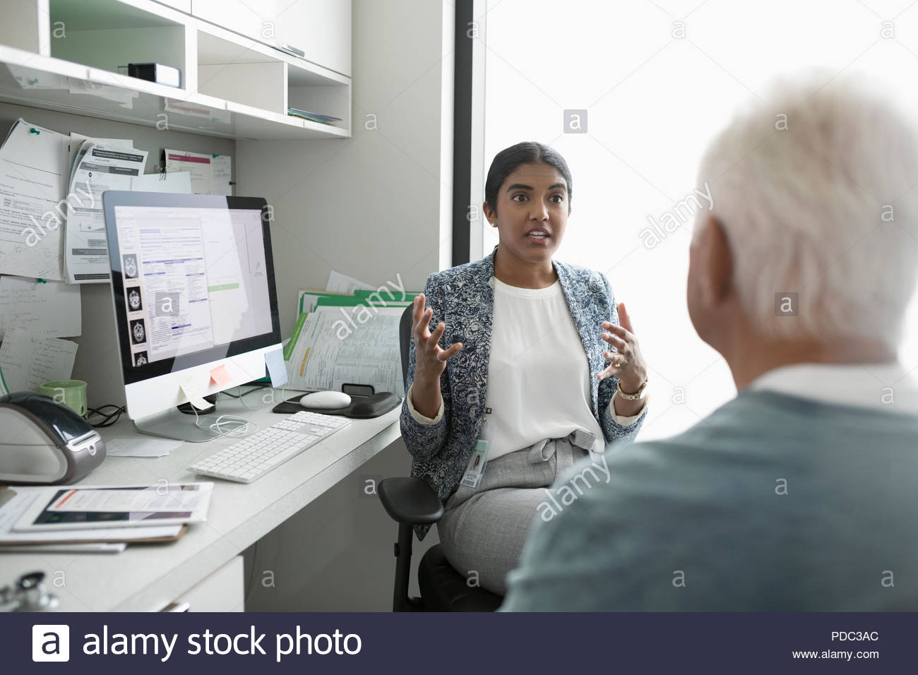 Female doctor talking with senior male patient in clinic office Stock Photo