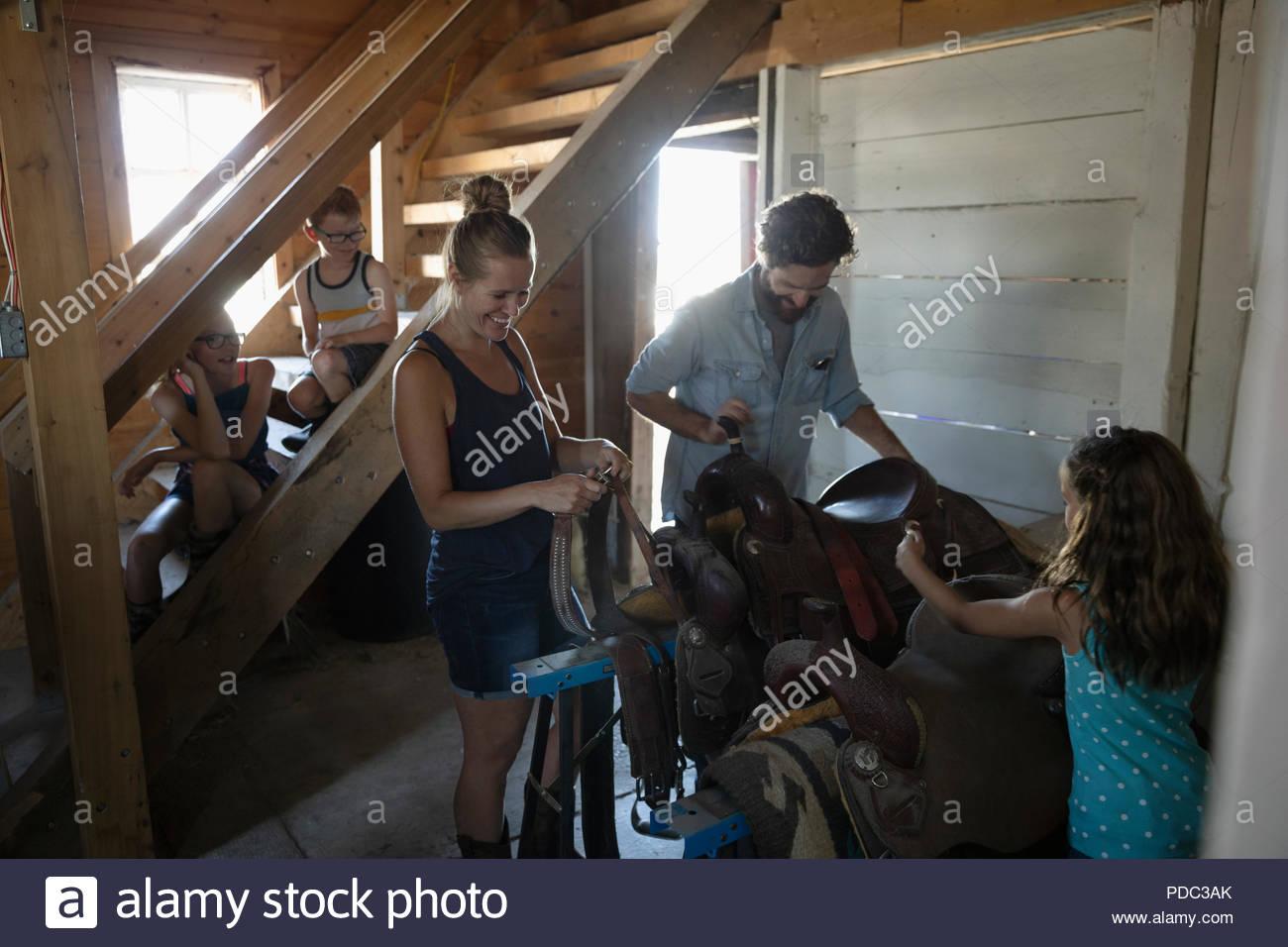 Family preparing saddles in barn - Stock Image