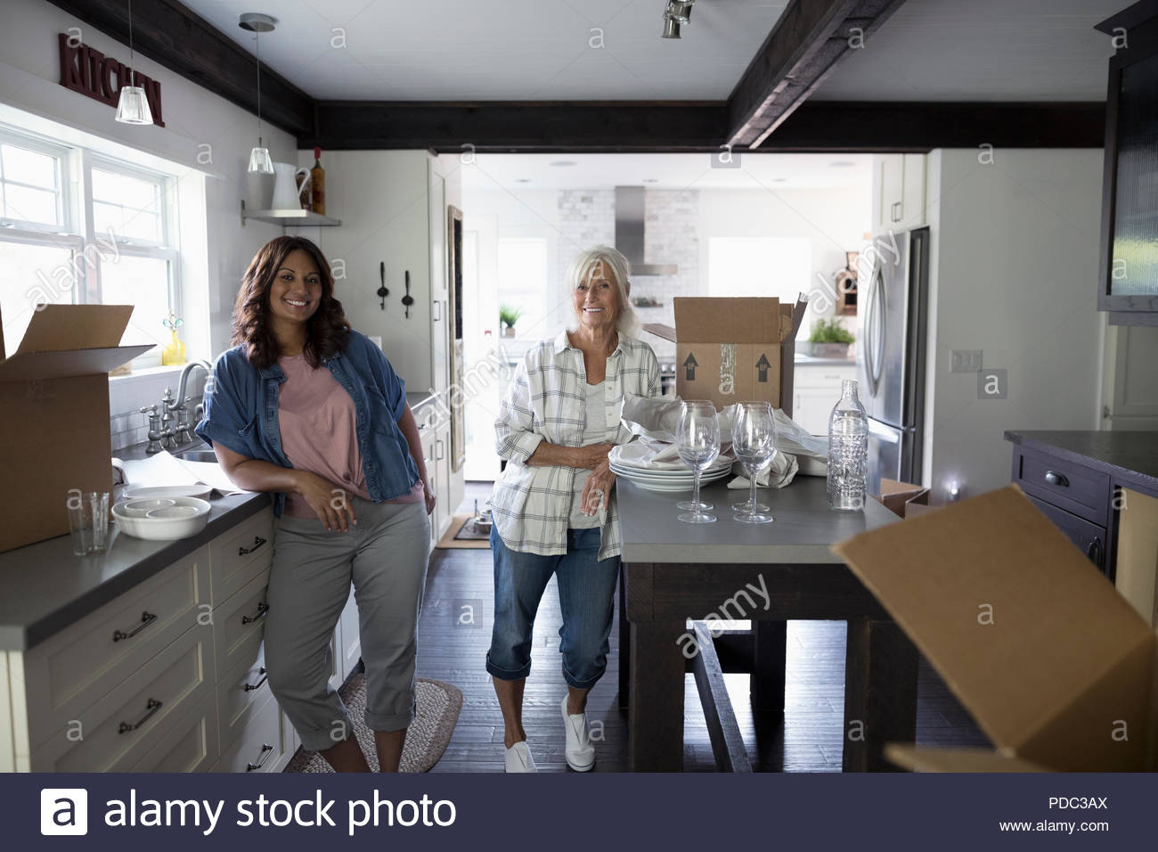 Portrait smiling daughter helping senior mother downsize, packing dishes in kitchen Stock Photo