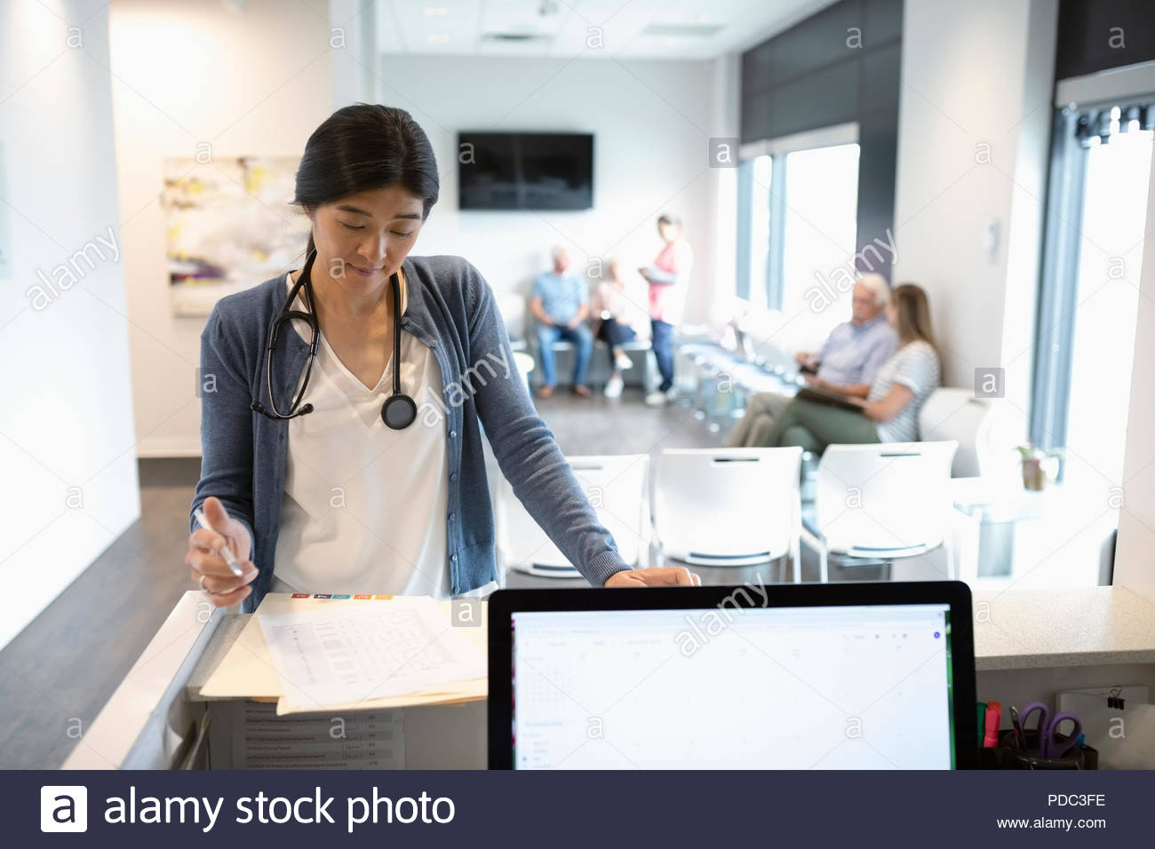Female doctor reviewing medical record at clinic reception desk - Stock Image