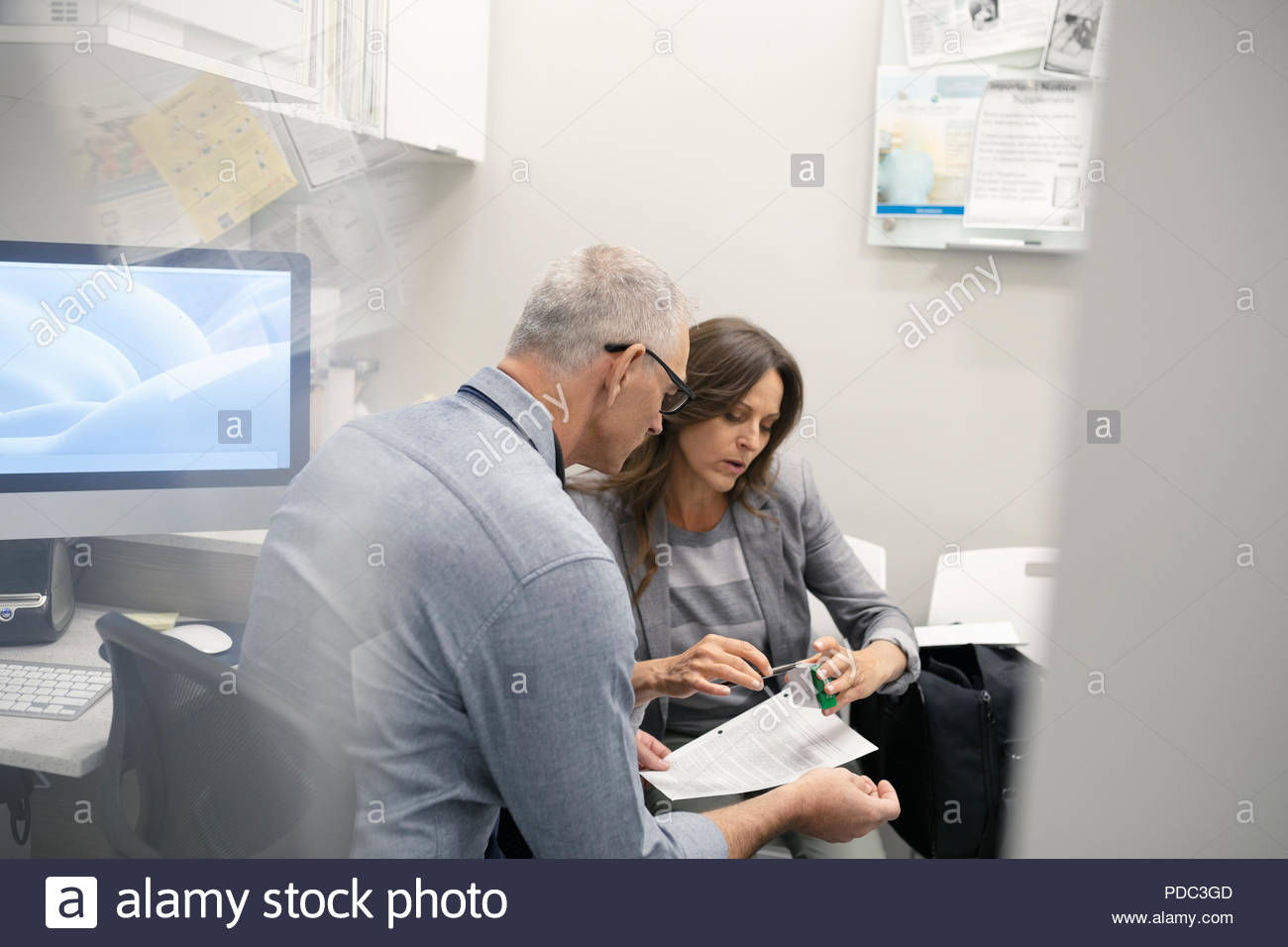Male doctor and female patient discussing medication in clinic office Stock Photo