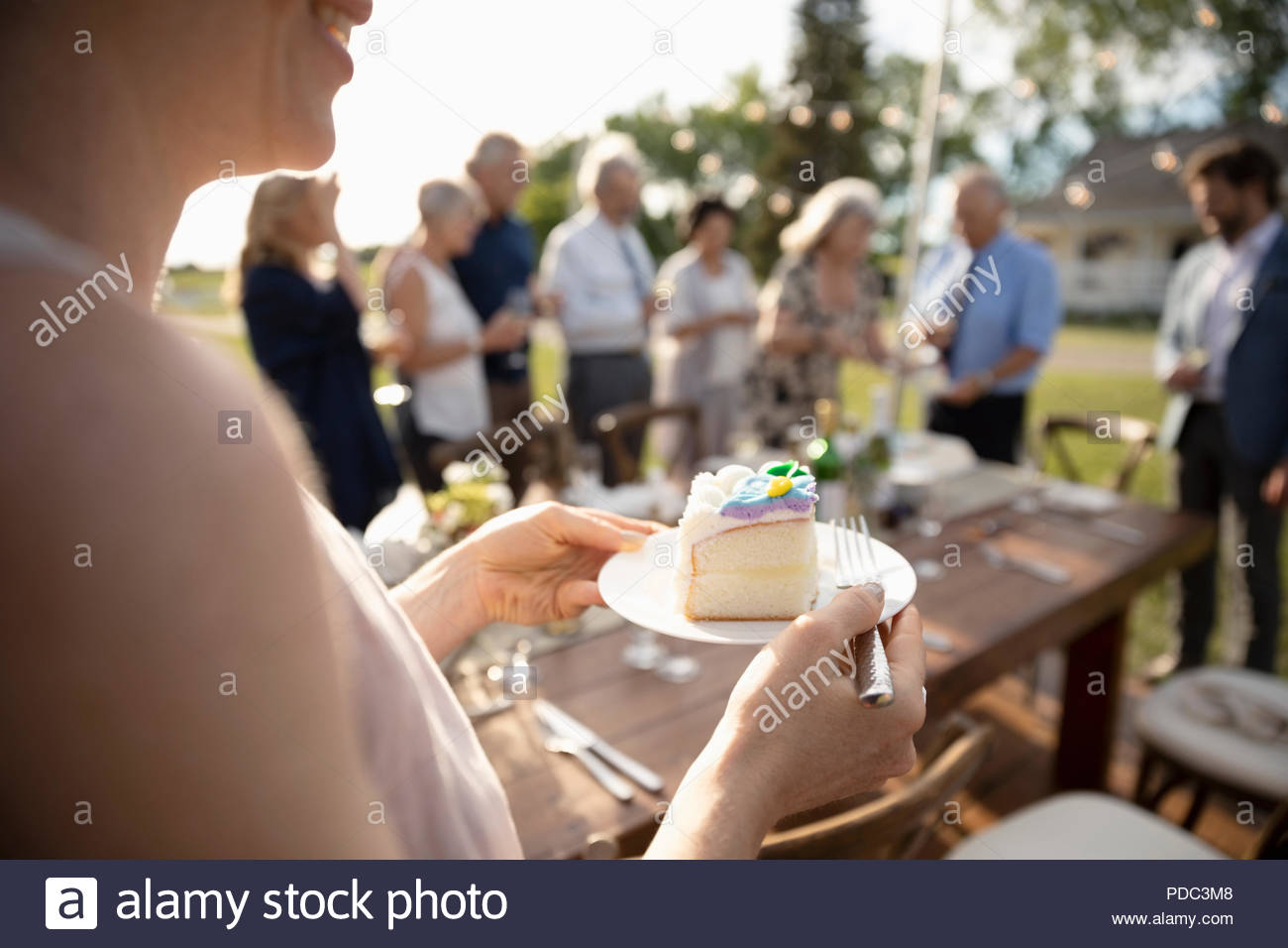 Woman eating cake, celebrating at sunny garden party with friends - Stock Image