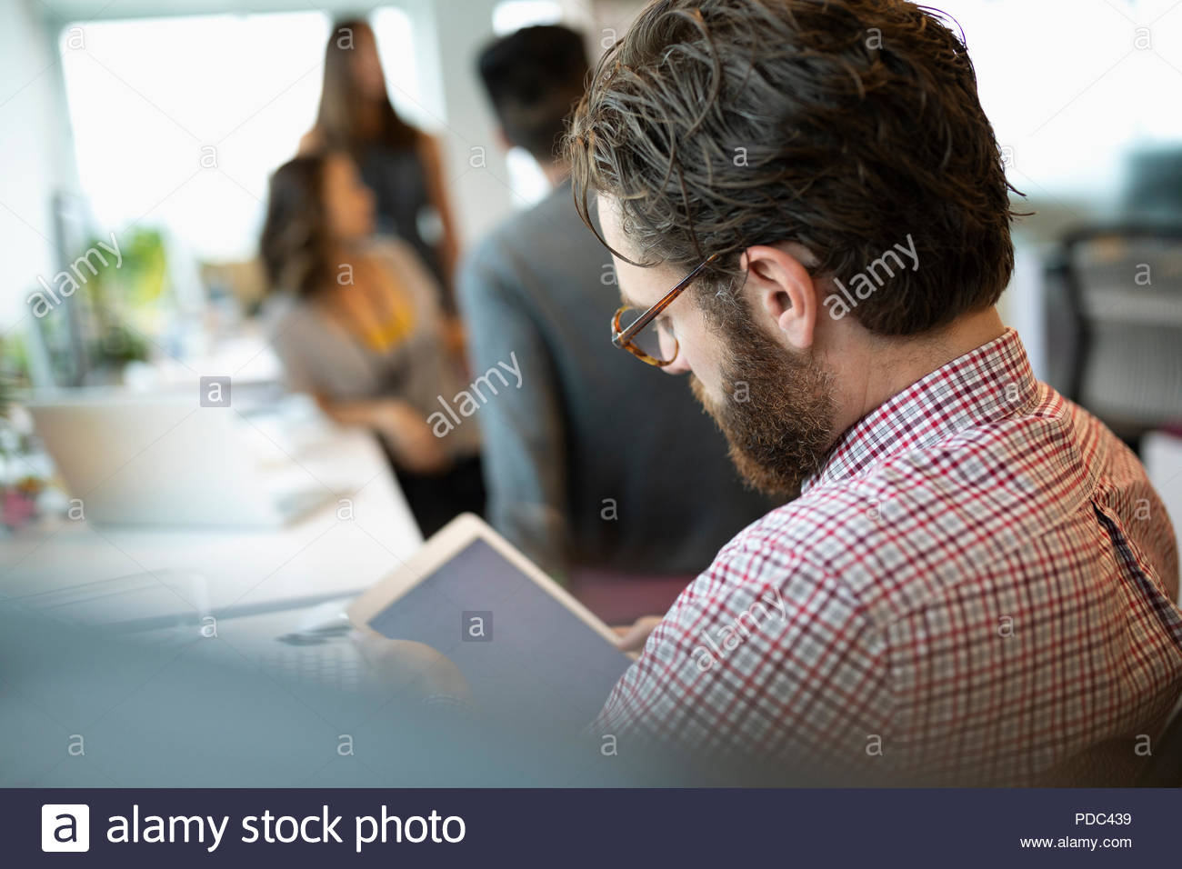 Focused businessman using digital tablet in office - Stock Image