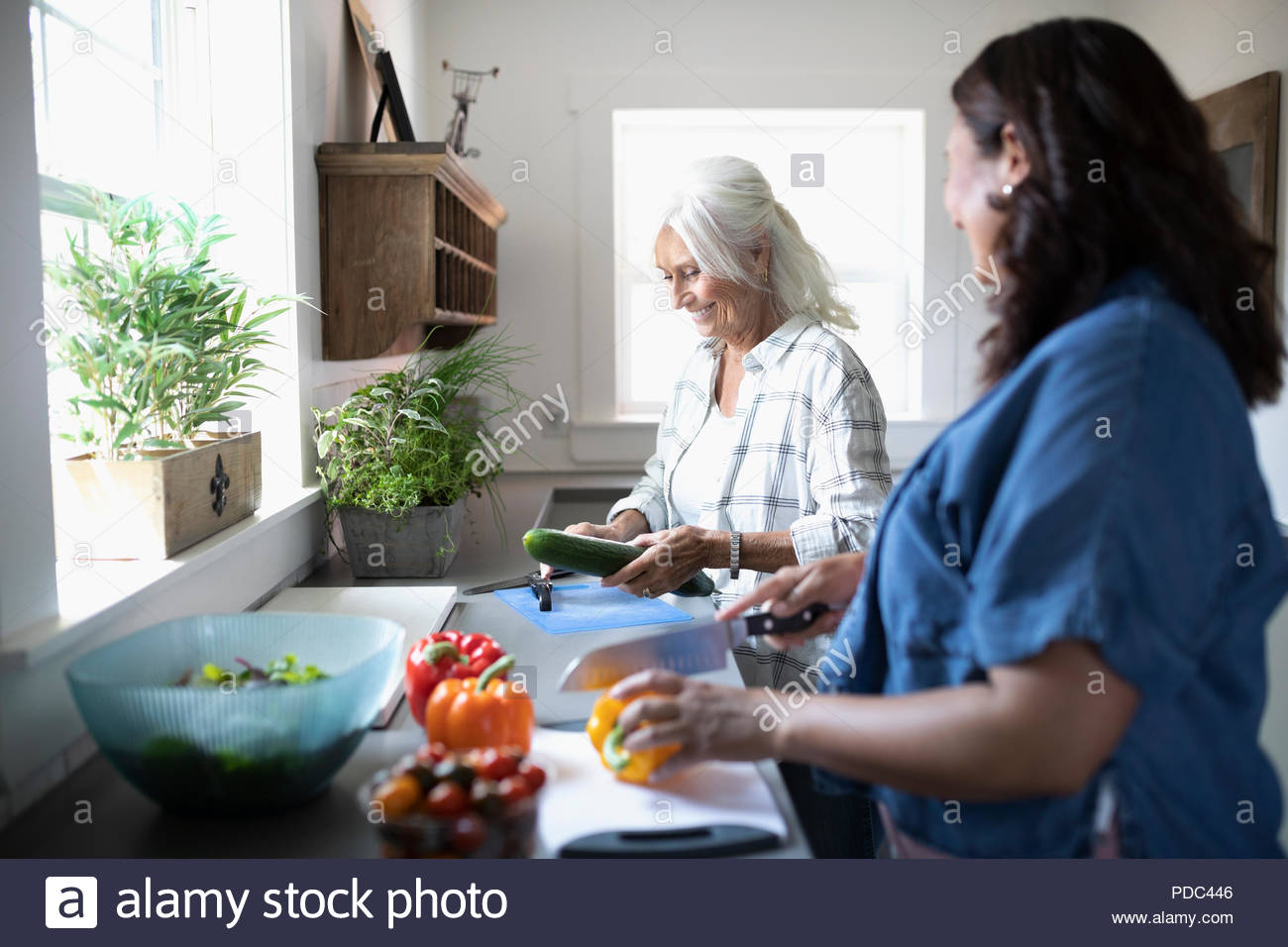 Daughter and senior mother cooking, cutting vegetables in kitchen - Stock Image