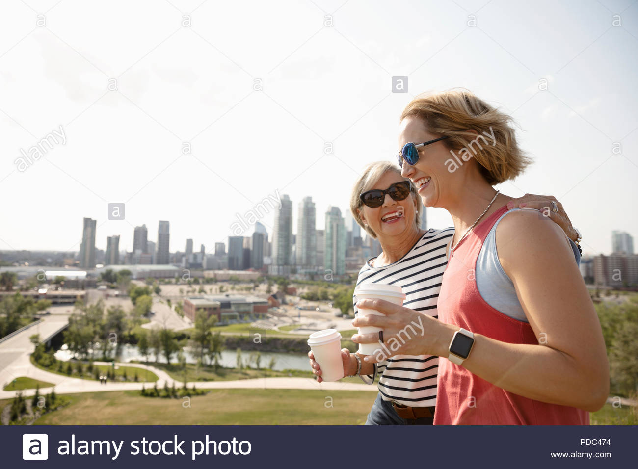 Smiling mother and daughter walking in sunny urban park with coffee Stock Photo