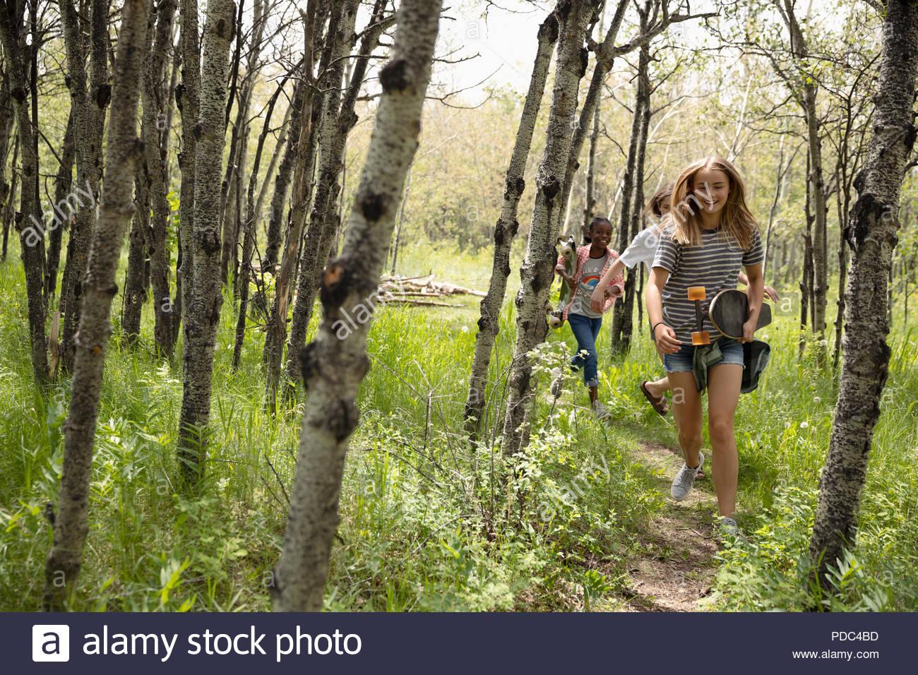 Tween girl friends running in sunny woods - Stock Image