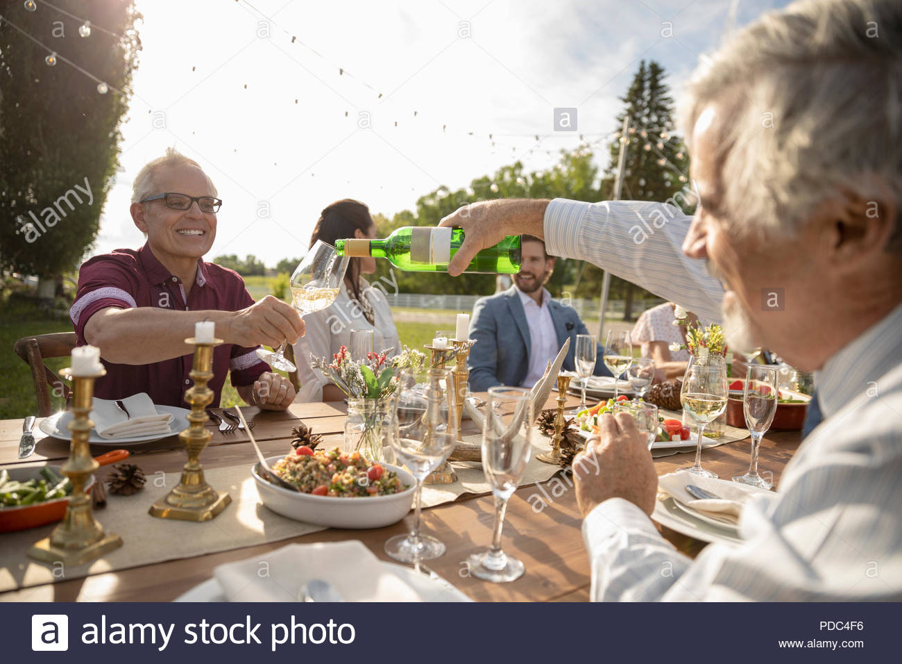 Man pouring wine for friend at wedding reception lunch table - Stock Image
