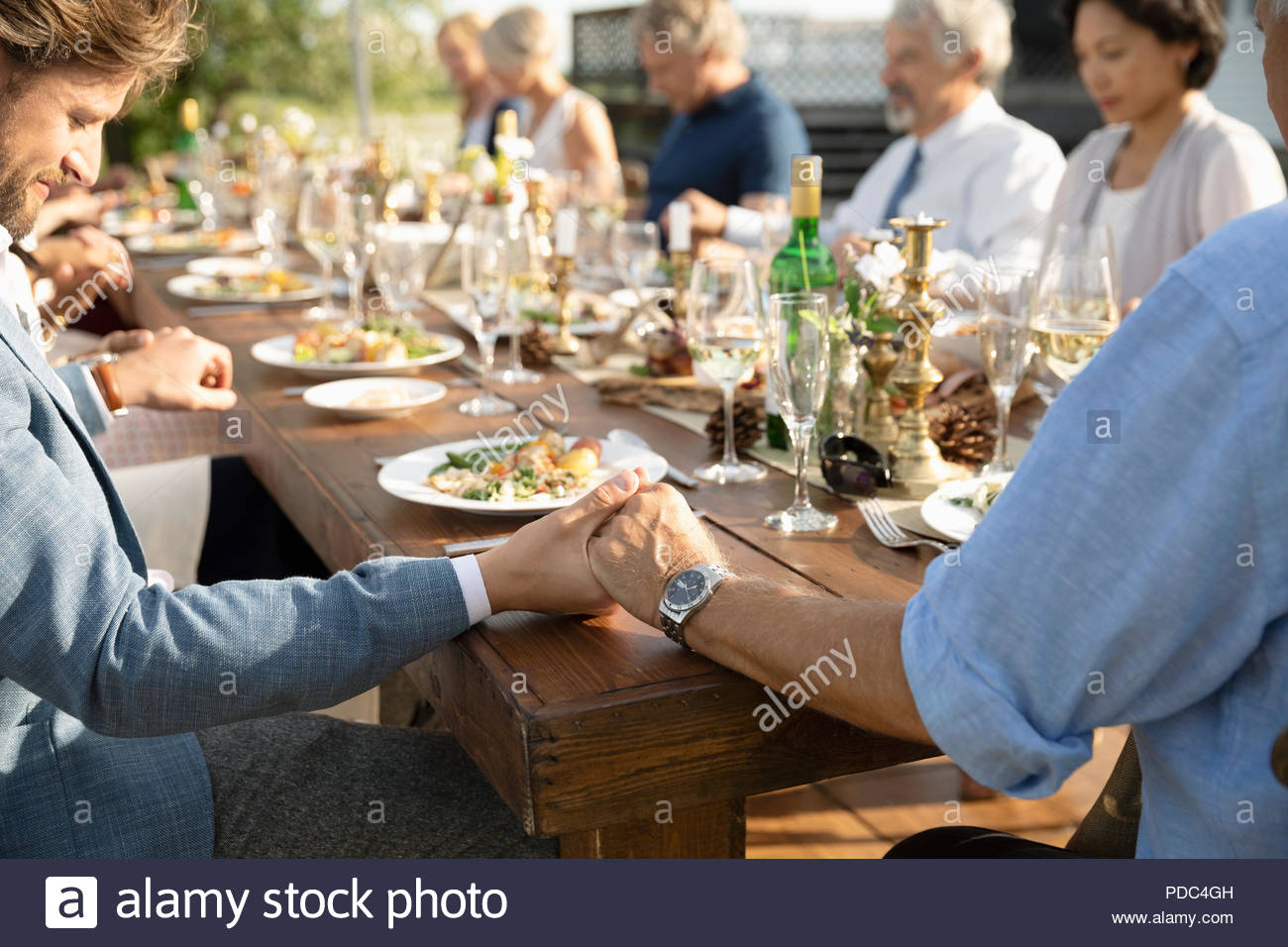 Father and son holding hands during prayer at garden party lunch - Stock Image