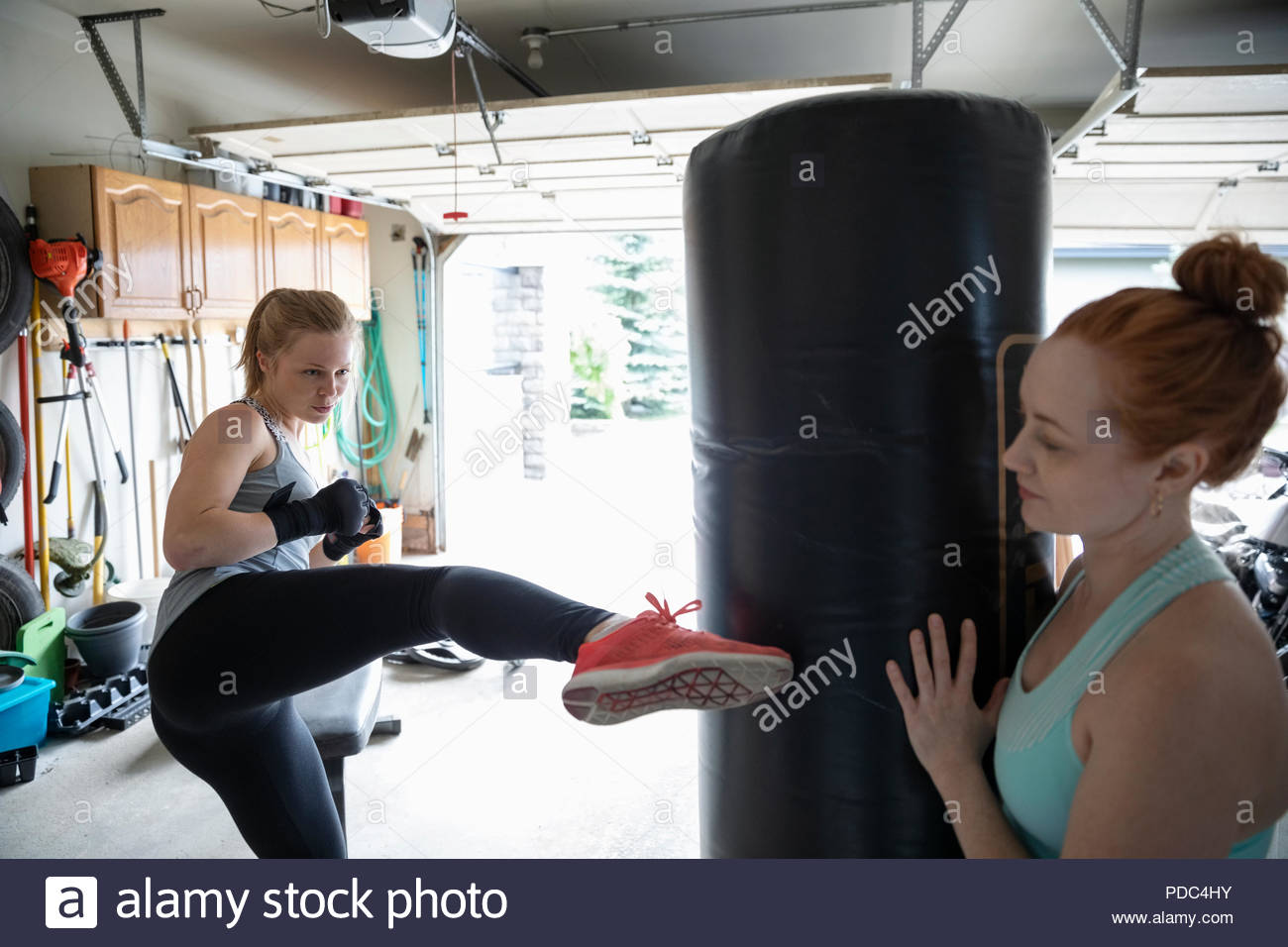 Young women friends kickboxing in garage - Stock Image