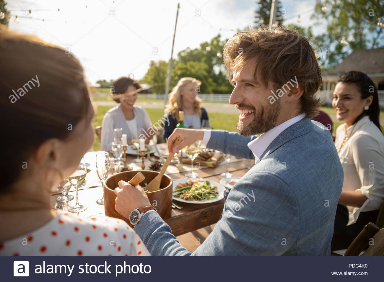 Smiling man serving salad at wedding reception lunch at sunny rural table - Stock Image