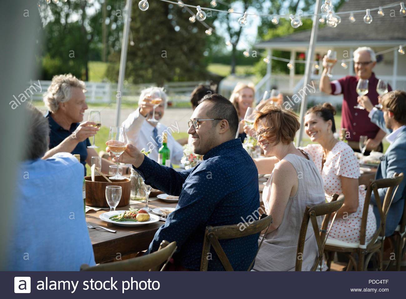 Friends enjoying celebratory toast at garden party table - Stock Image
