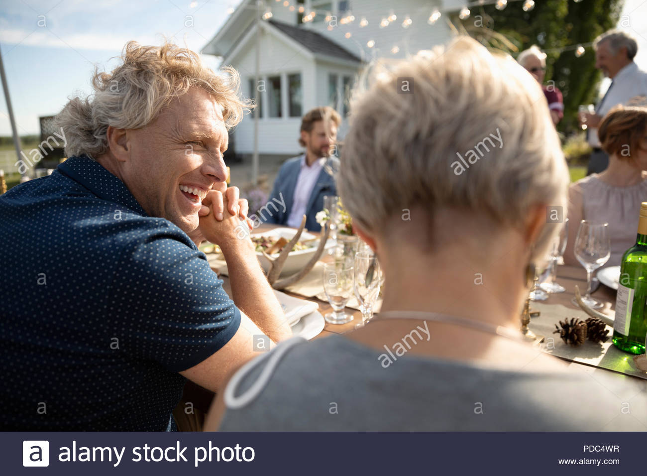 Smiling man enjoying wedding reception lunch in rural garden - Stock Image
