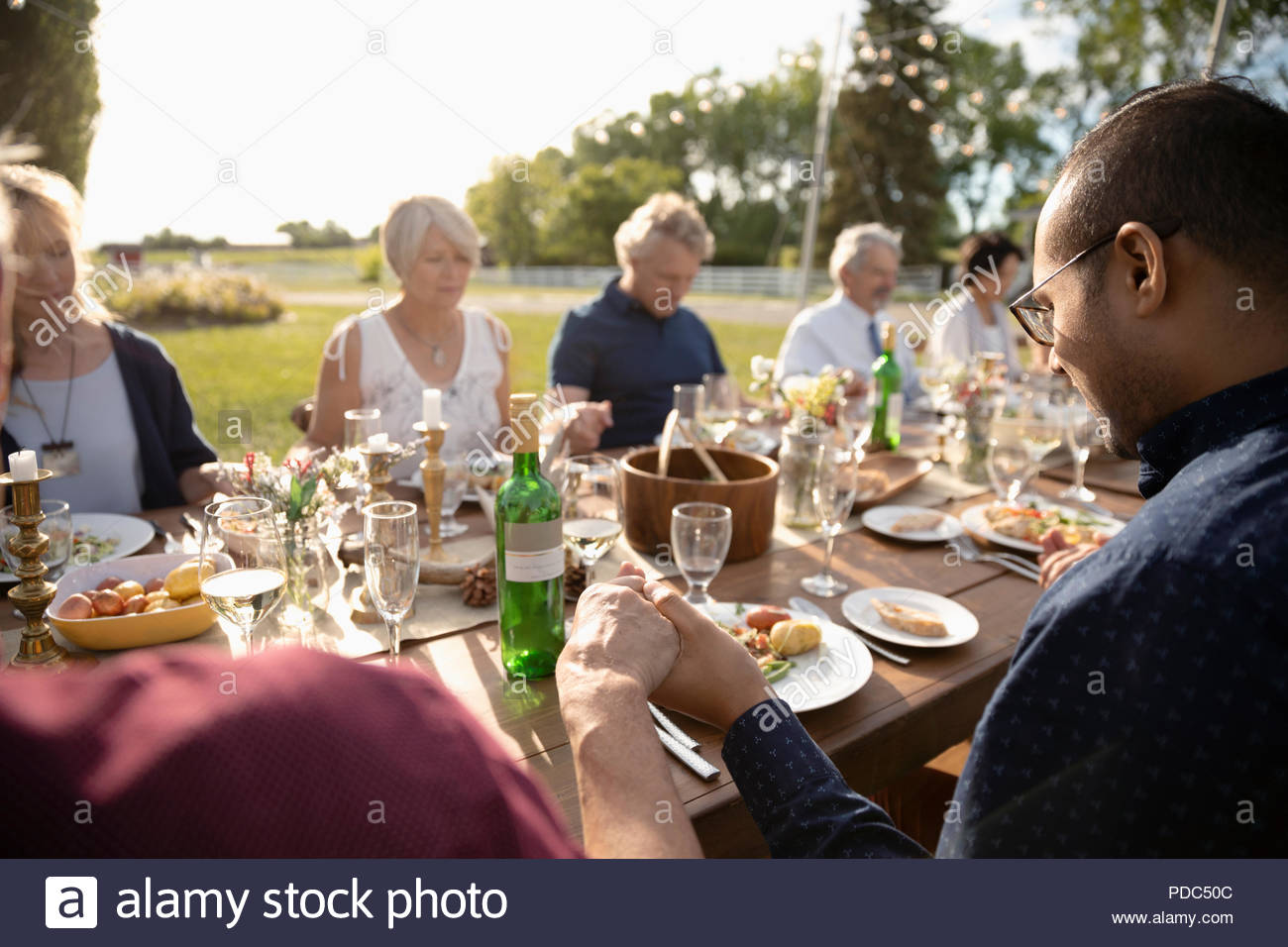 Friends praying, holding hands at sunny garden party lunch - Stock Image