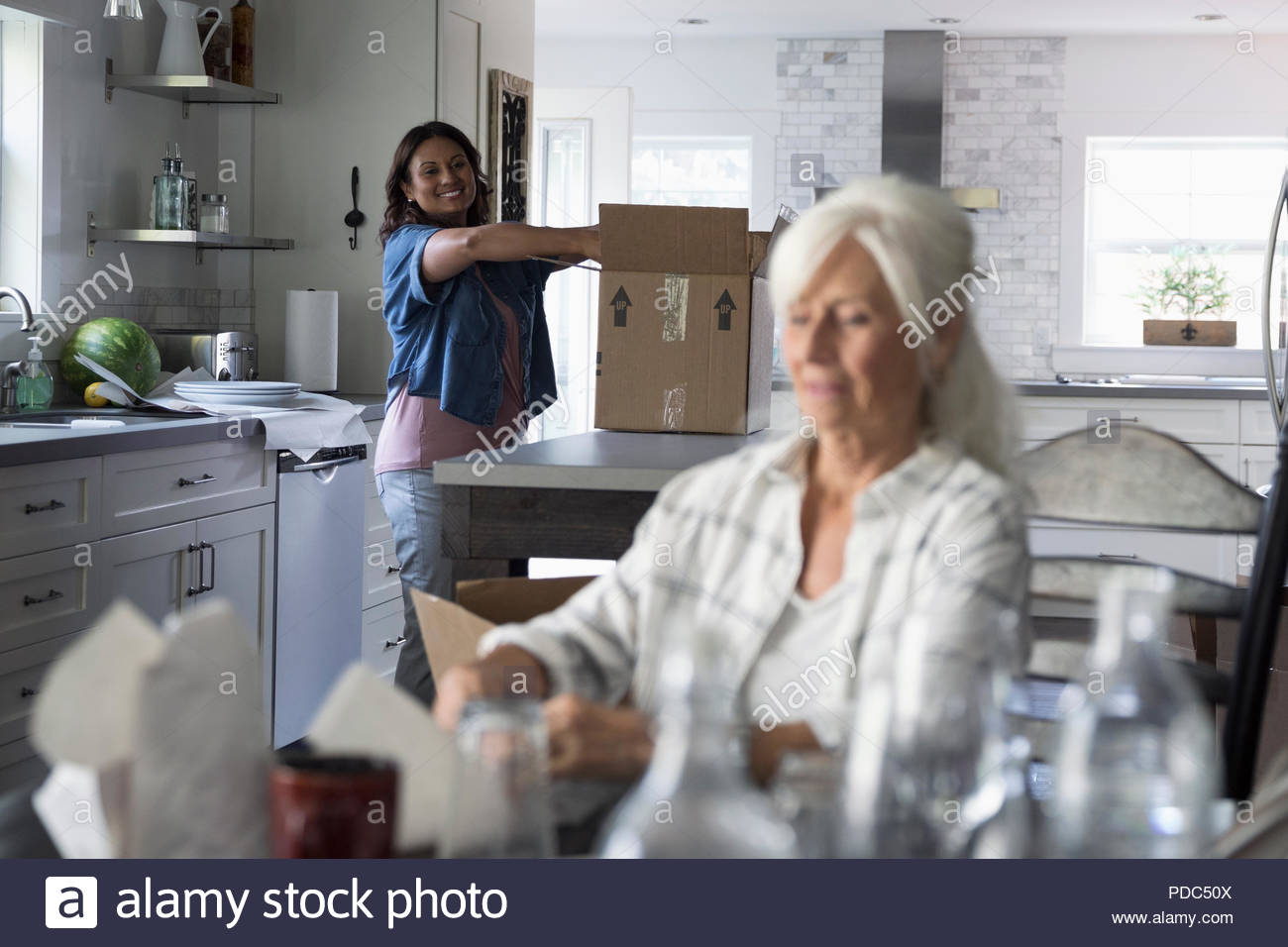Daughter helping senior mother downsize, packing dishes in kitchen Stock Photo