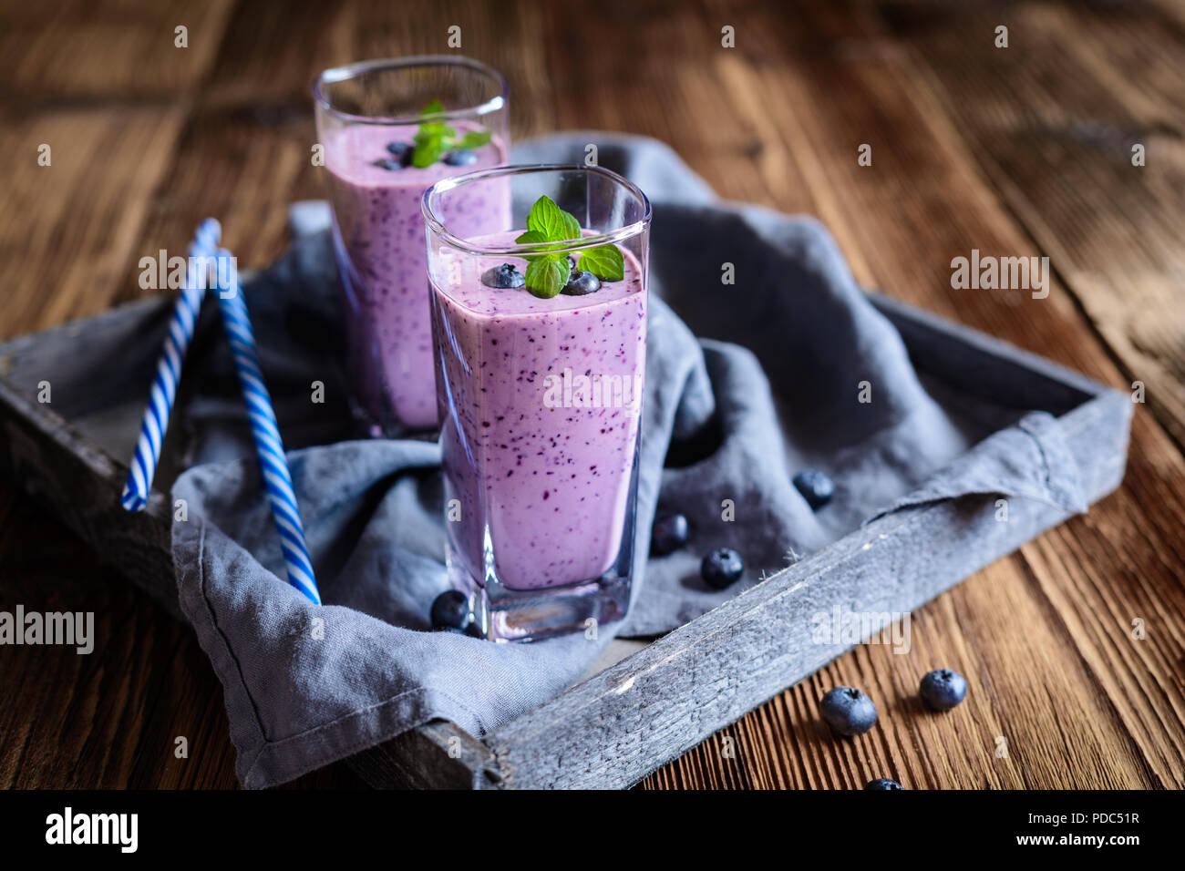 Healthy blueberry milkshake in glass jars - Stock Image