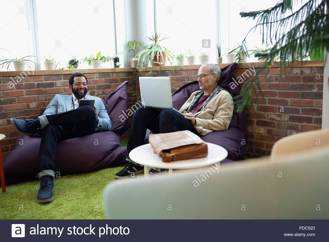 Creative businessmen using digital tablet and laptop on beanbags in office - Stock Image
