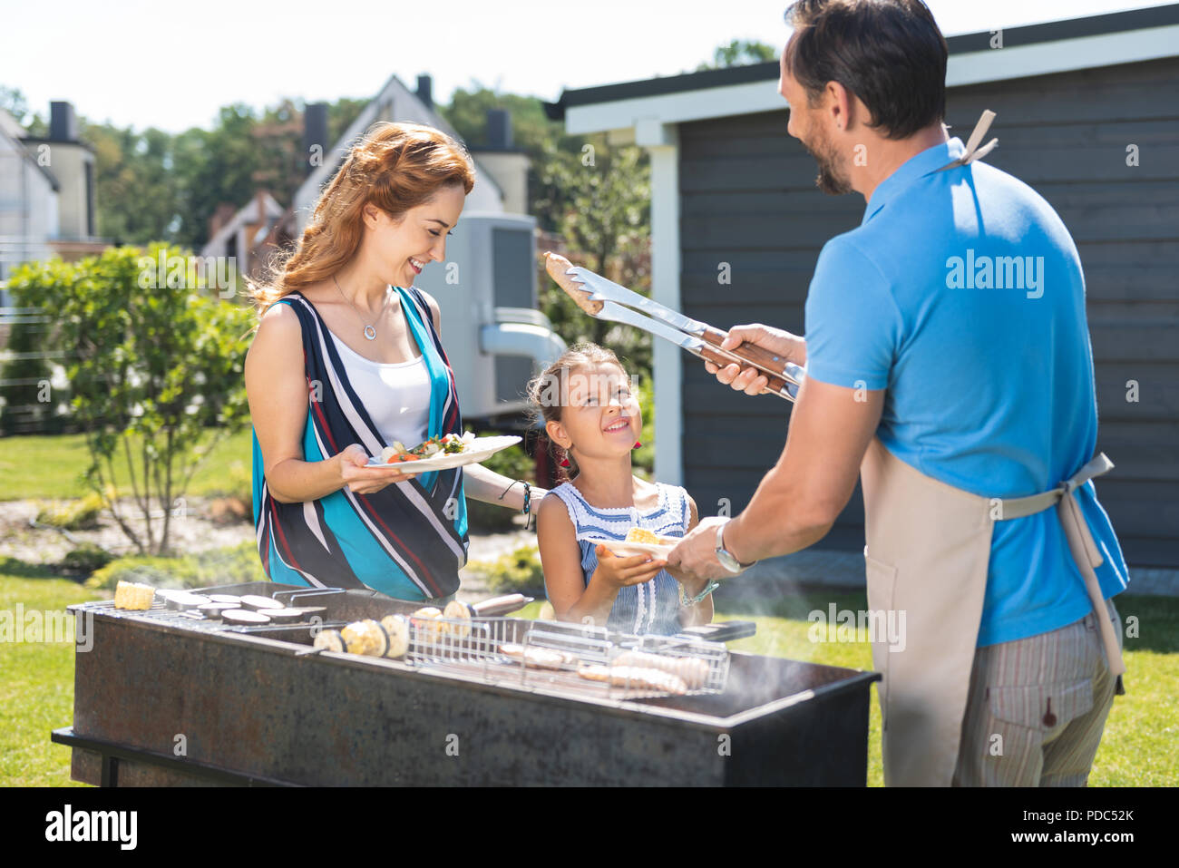 Nice pleasant man holding sausages - Stock Image
