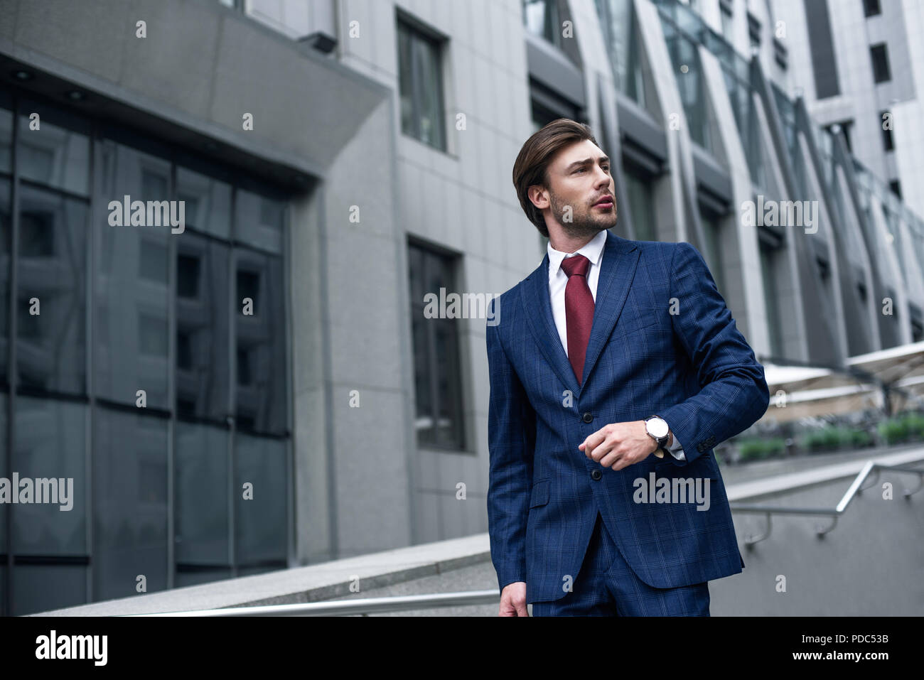 e1587bfe3eb4 Confident businessman. Confident young man in full suit adjusting his  sleeve and looking away while