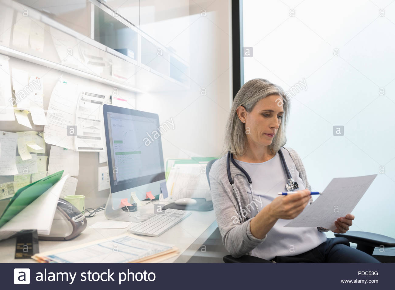 Female doctor reviewing paperwork in clinic office - Stock Image