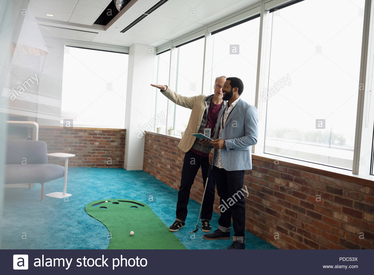 Creative businessman talking, practicing putting in office - Stock Image
