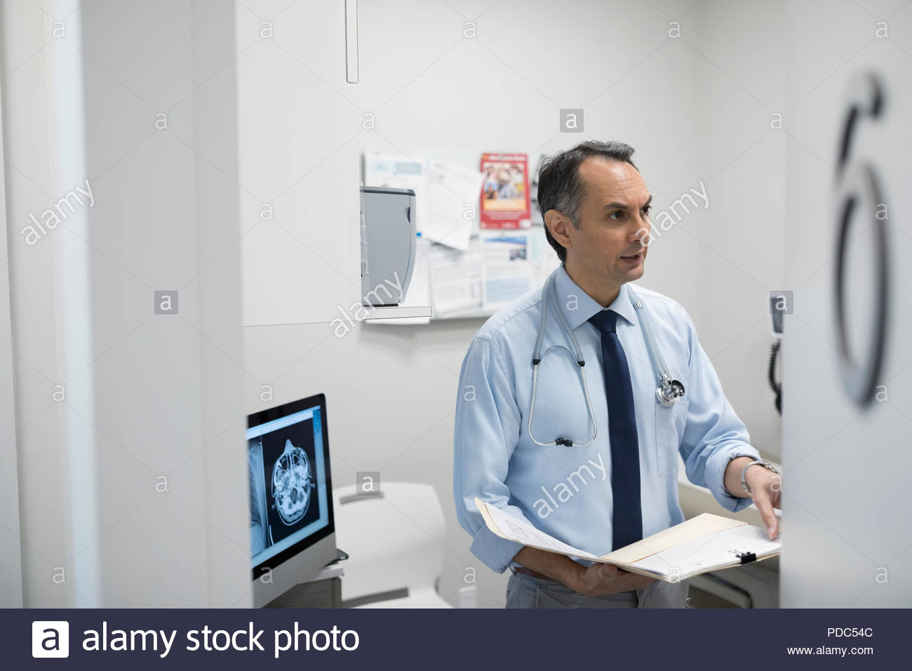 Male doctor discussing medical record in clinic exam room - Stock Image