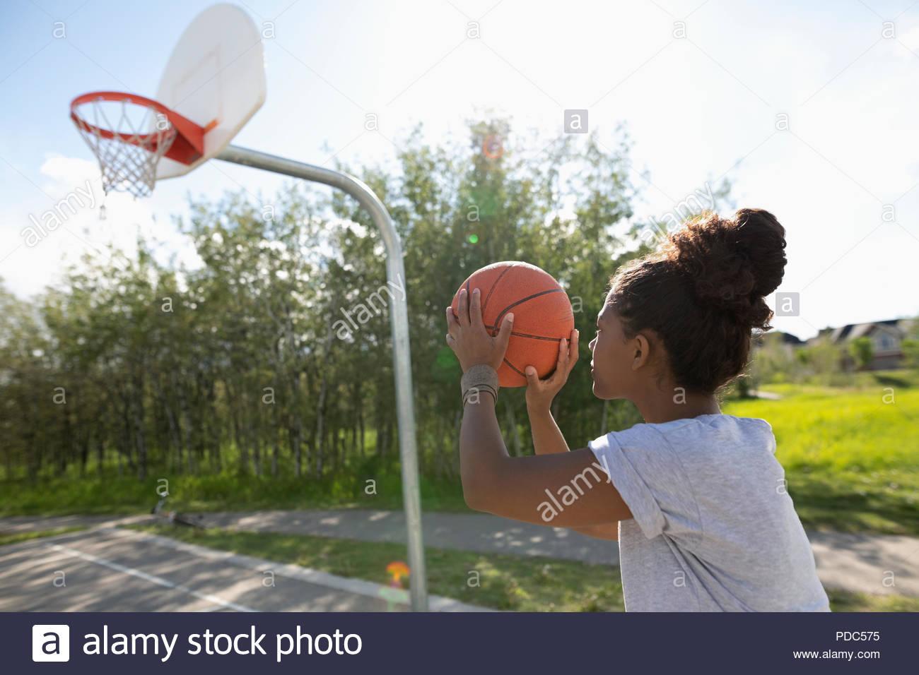 Young woman playing basketball at park basketball court - Stock Image