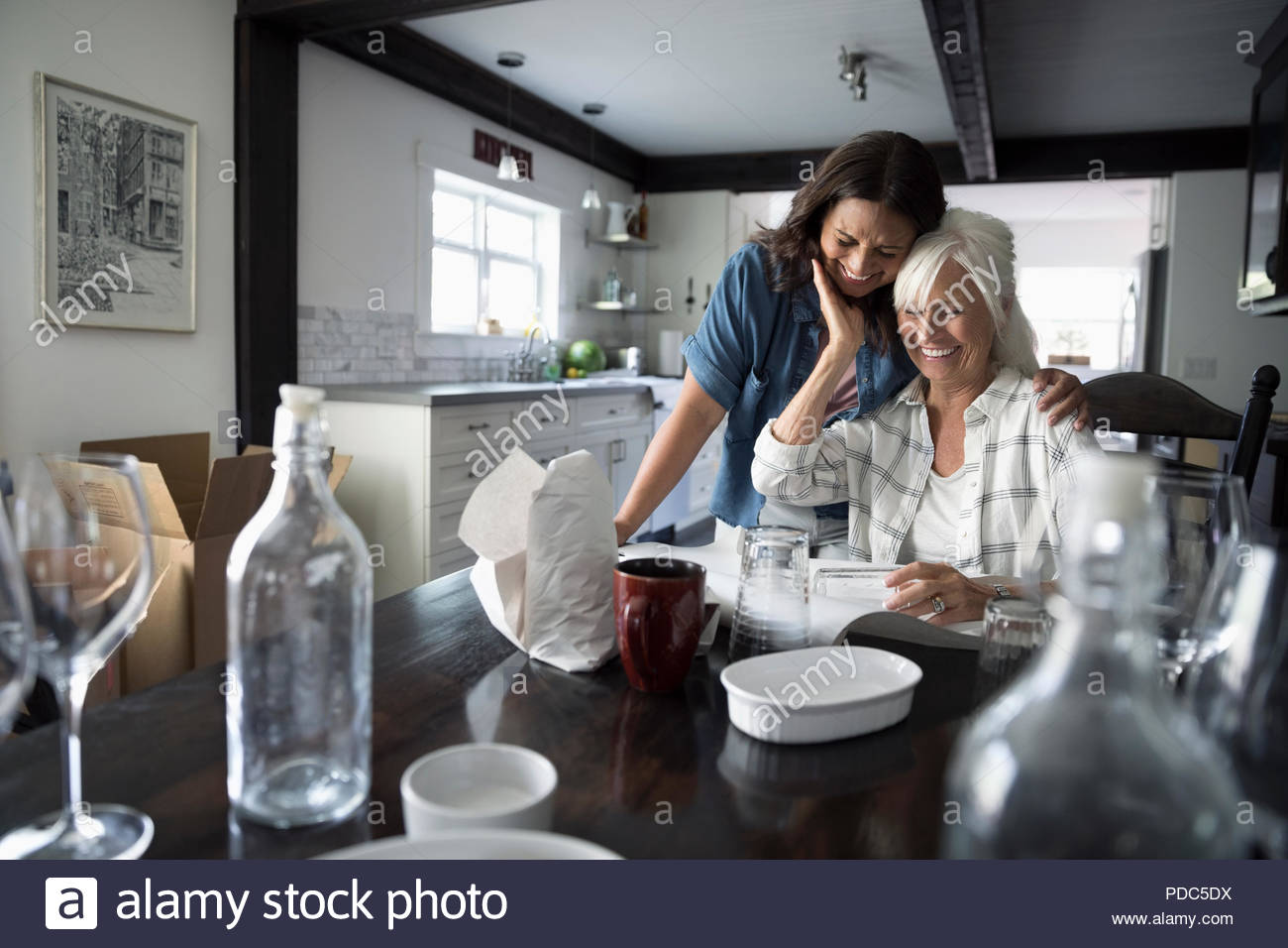 Affectionate daughter helping senior mother downsize, packing dishes - Stock Image