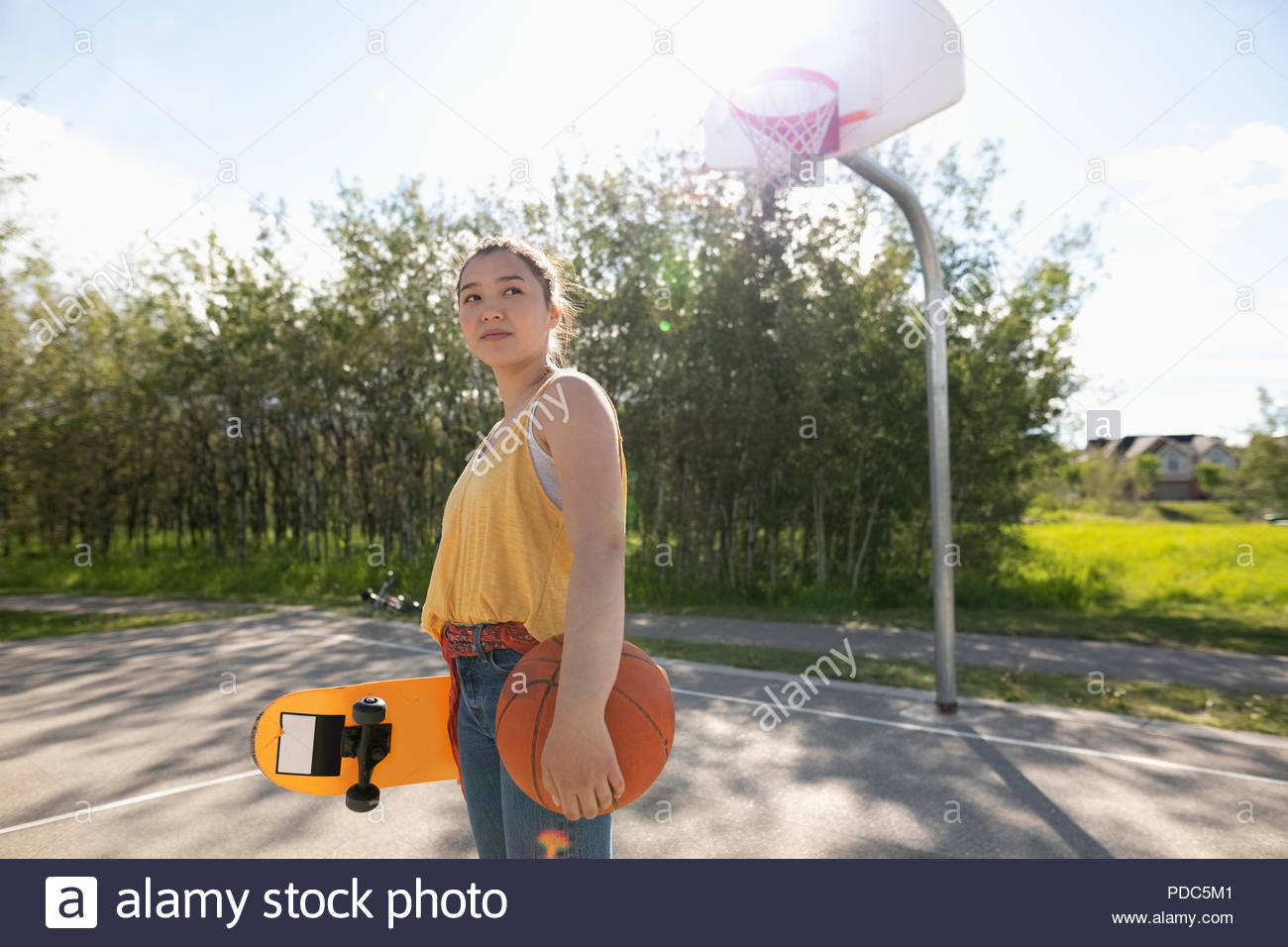 Confident, cool teenage girl with skateboard and basketball on sunny park basketball court - Stock Image
