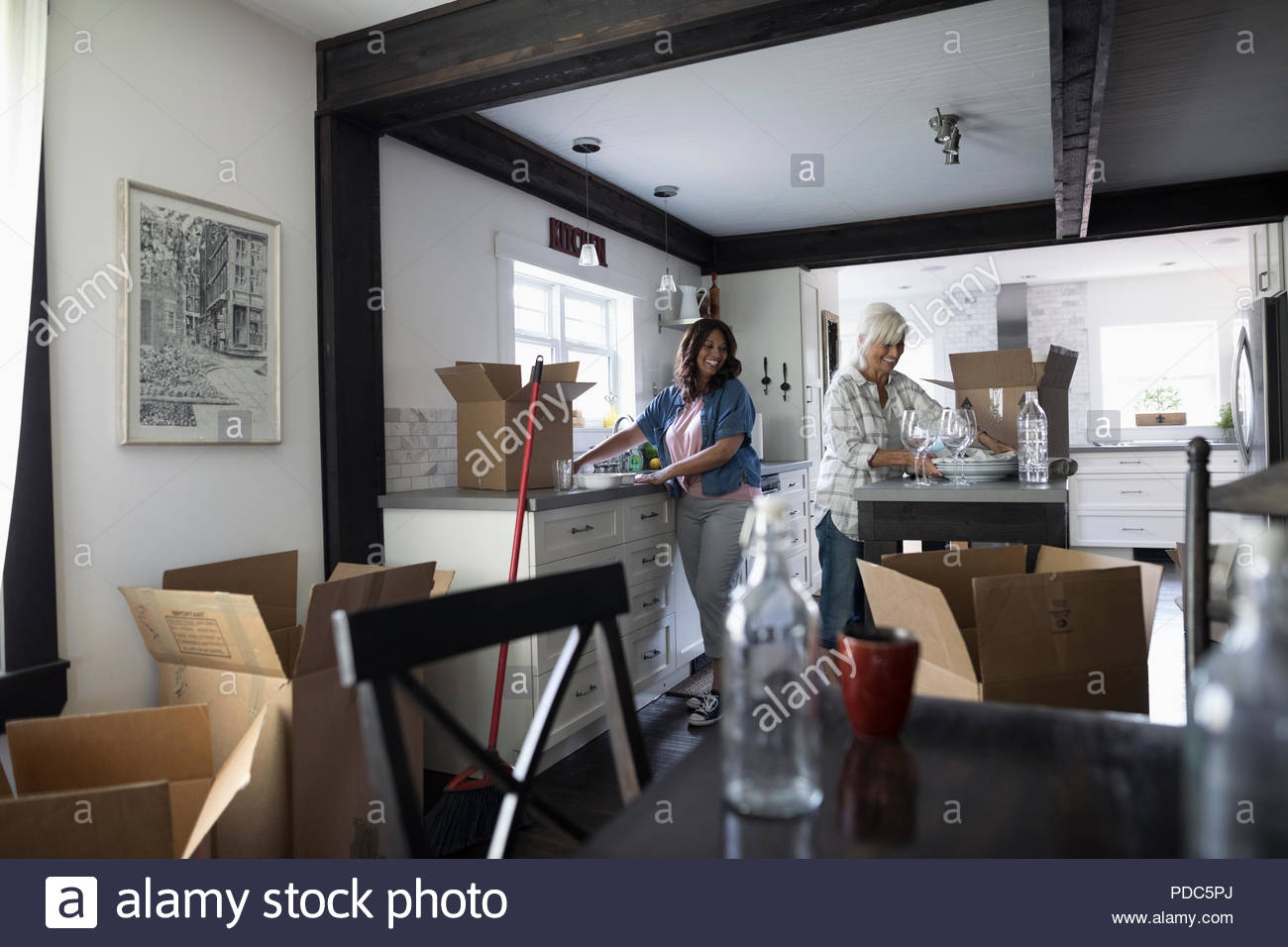Daughter helping senior mother downsize, packing dishes in kitchen - Stock Image