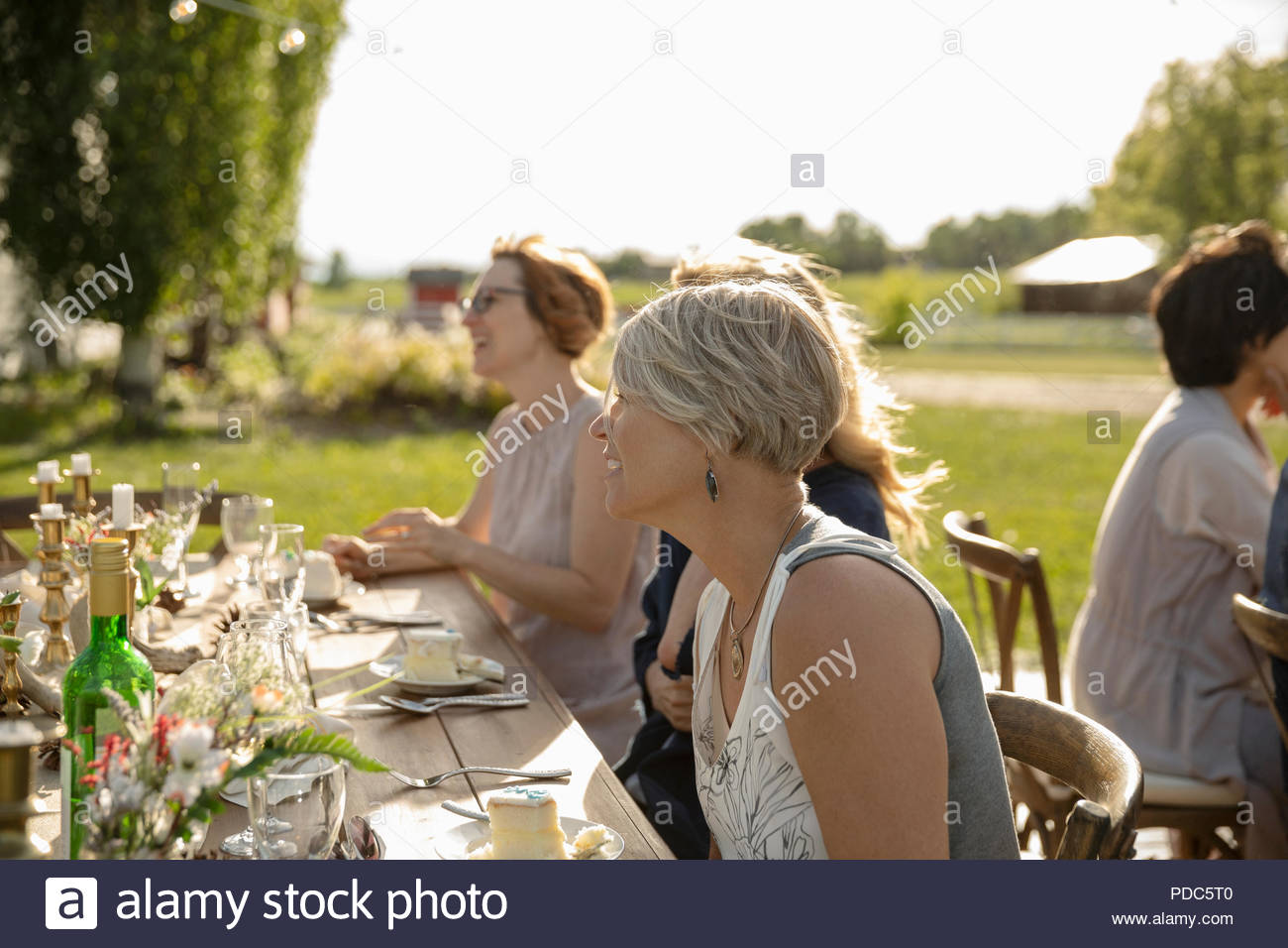 Smiling woman eating cake at garden party table - Stock Image