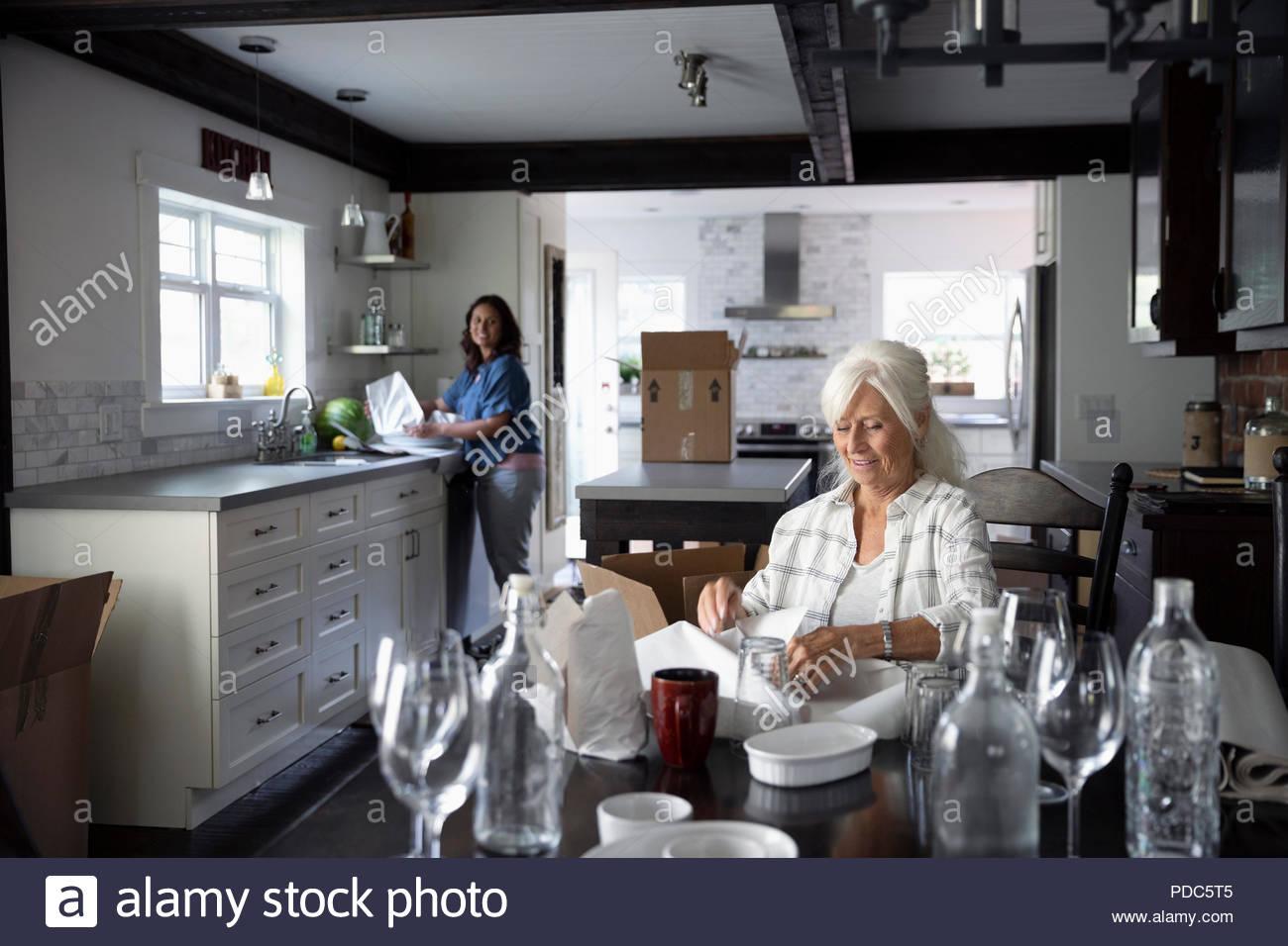 Senior woman downsizing, packing dishes - Stock Image