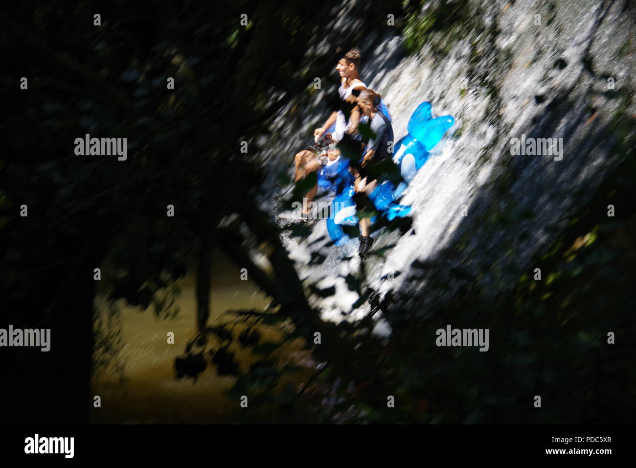 Teenagers Sliding Down a Concrete Waterfall on Inflatables During a Heat Wave. The Byes Riverside Park, Sidmouth, East Devon, UK. August, 2018. - Stock Image