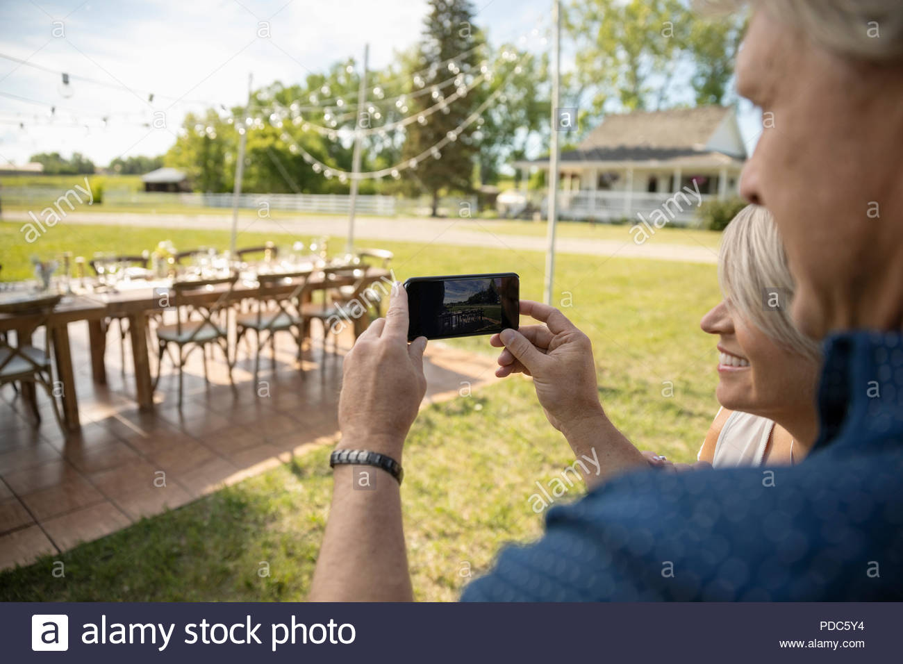 Mature couple with camera phone photographing wedding reception table in rural garden - Stock Image