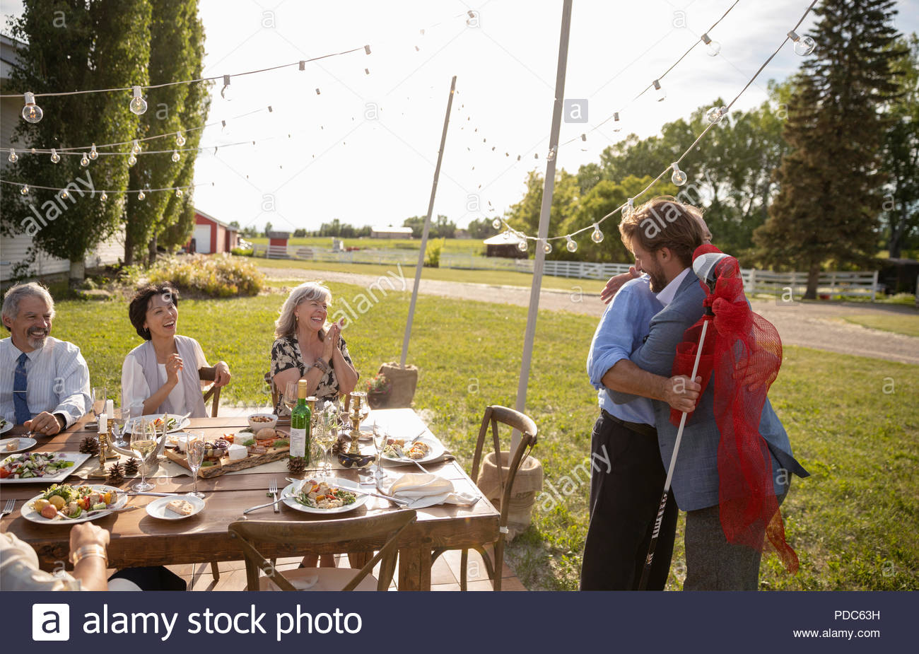 Friends clapping for son giving golf club to father at retirement party in sunny rural garden - Stock Image