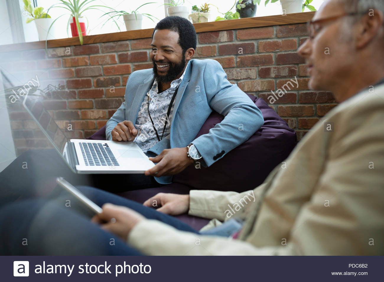 Smiling creative businessmen using digital tablet and laptop on beanbags in office - Stock Image