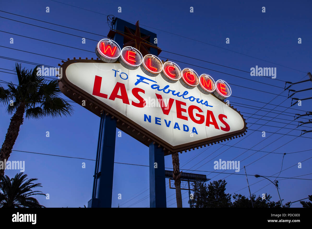 Welcome to Fabulous Las Vegas sign, palm trees and overhead wire grid at night. - Stock Image