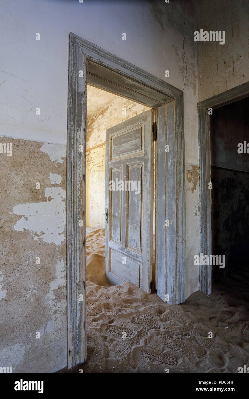 Sand consumes a building at Kolmanskop, a former diamond-mining town abandoned to the Namib desert in the 1950s. - Stock Image
