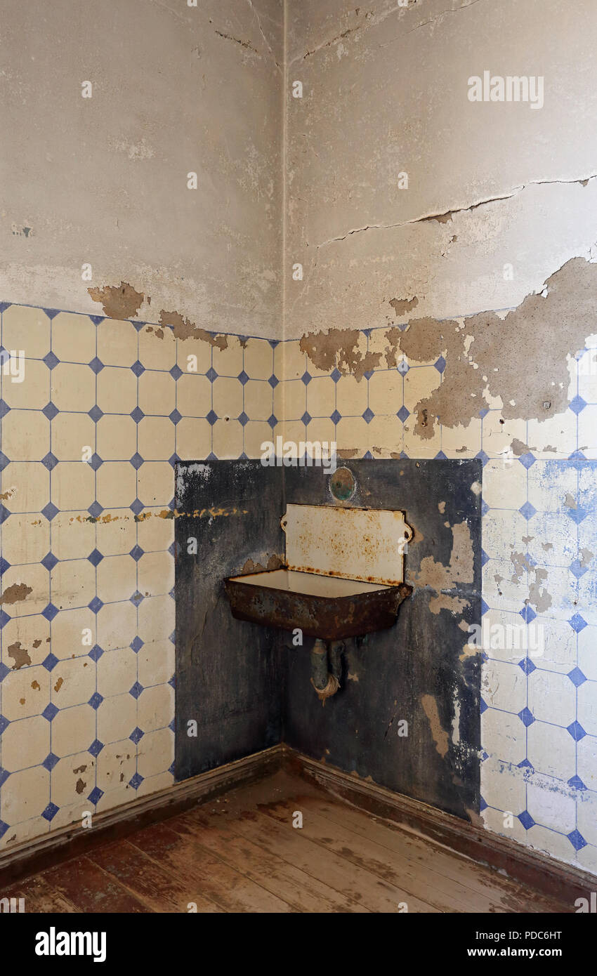 A rusty old wash basin inside a building at Kolmanskop, a former diamond-mining town abandoned to the Namib desert in the 1950s. - Stock Image