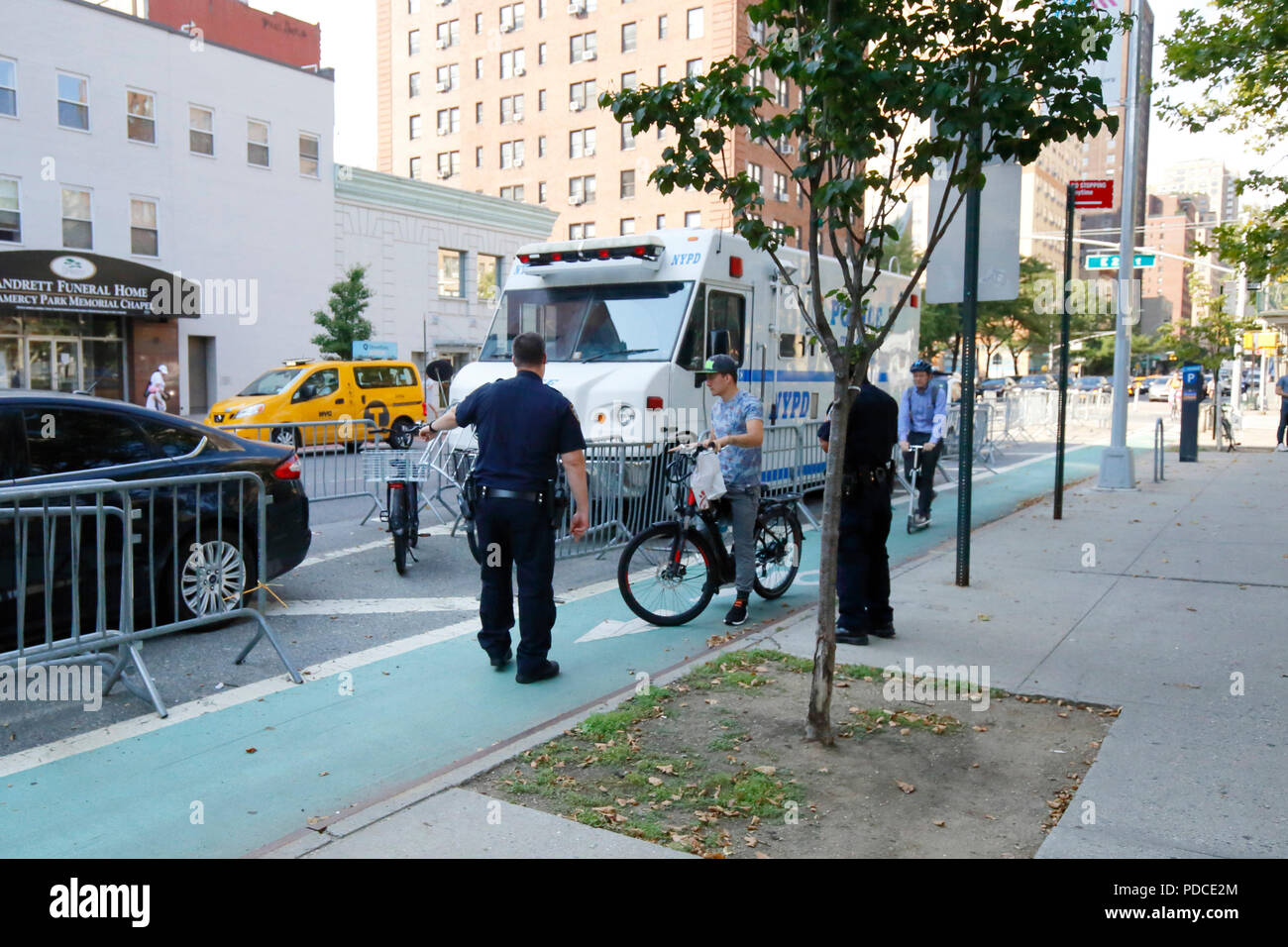 New York, NY, USA. 8th August, 2018.  Police direct a cyclist with a Class 2 electric bicycle--throttle assist--to a holding cage next to the Second Avenue bike lane in Manhattan. Electric bikes are currently illegal in New York State. NYC Mayor De Blasio has directed the Department of Transportation to begin allowing Class 1 pedal assisted electric bikes, while continuing the crackdown on all e bikes.  Most electric bike users are food delivery personnel. Stock Photo