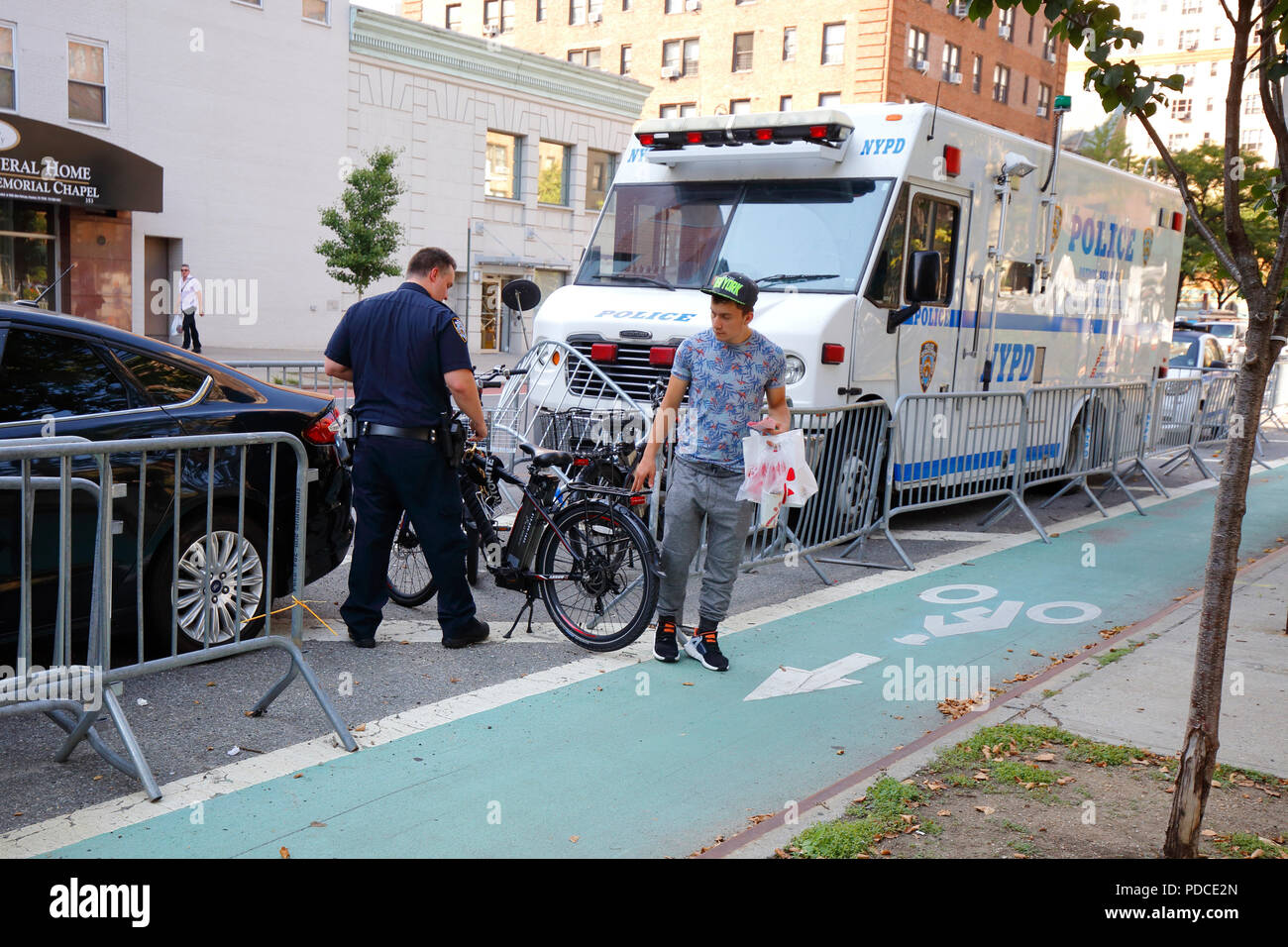 New York, NY, USA. 8th August, 2018.  Police examine a confiscated Class 2--throttle assist--electric bicycle, while a cyclist lingers briefly for a final parting touch. Electric bikes are currently illegal in New York State. NYC Mayor De Blasio has directed the Department of Transportation to begin allowing Class 1 pedal assisted electric bikes, while continuing the crackdown on all e bikes.  Most electric bike users are food delivery personnel. Stock Photo