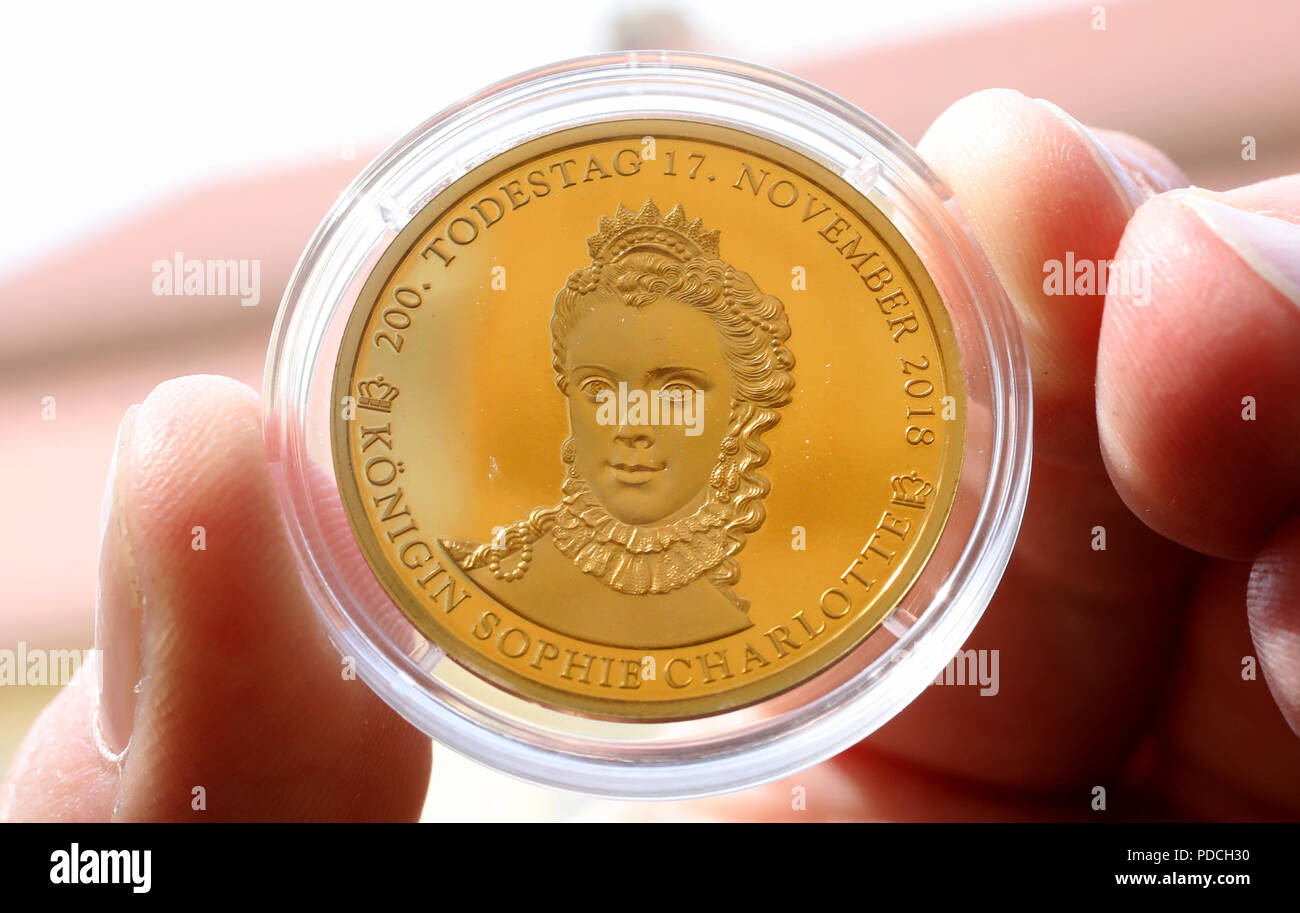 """08 August 2018, Germany, Mirow: One of the strictly limited commemorative coins in gold commemorating the 200th anniversary of the death of British Queen Sophie Charlotte (1744-1818) shows Michael Knippschild of Euromint (Bochum), after they were presented at a reception in the """"3 Queen Palais"""" in the Kavaliershaus. The monarch came from Mecklenburg-Strelitz and headed Great Britain and Ireland for 57 years. She is counted among the founders of today's British royal family. (presented on """"Special coins for ancestor of the English royal family"""" of 08.08.2018) Photo: Bernd Wüstneck/dpa Stock Photo"""