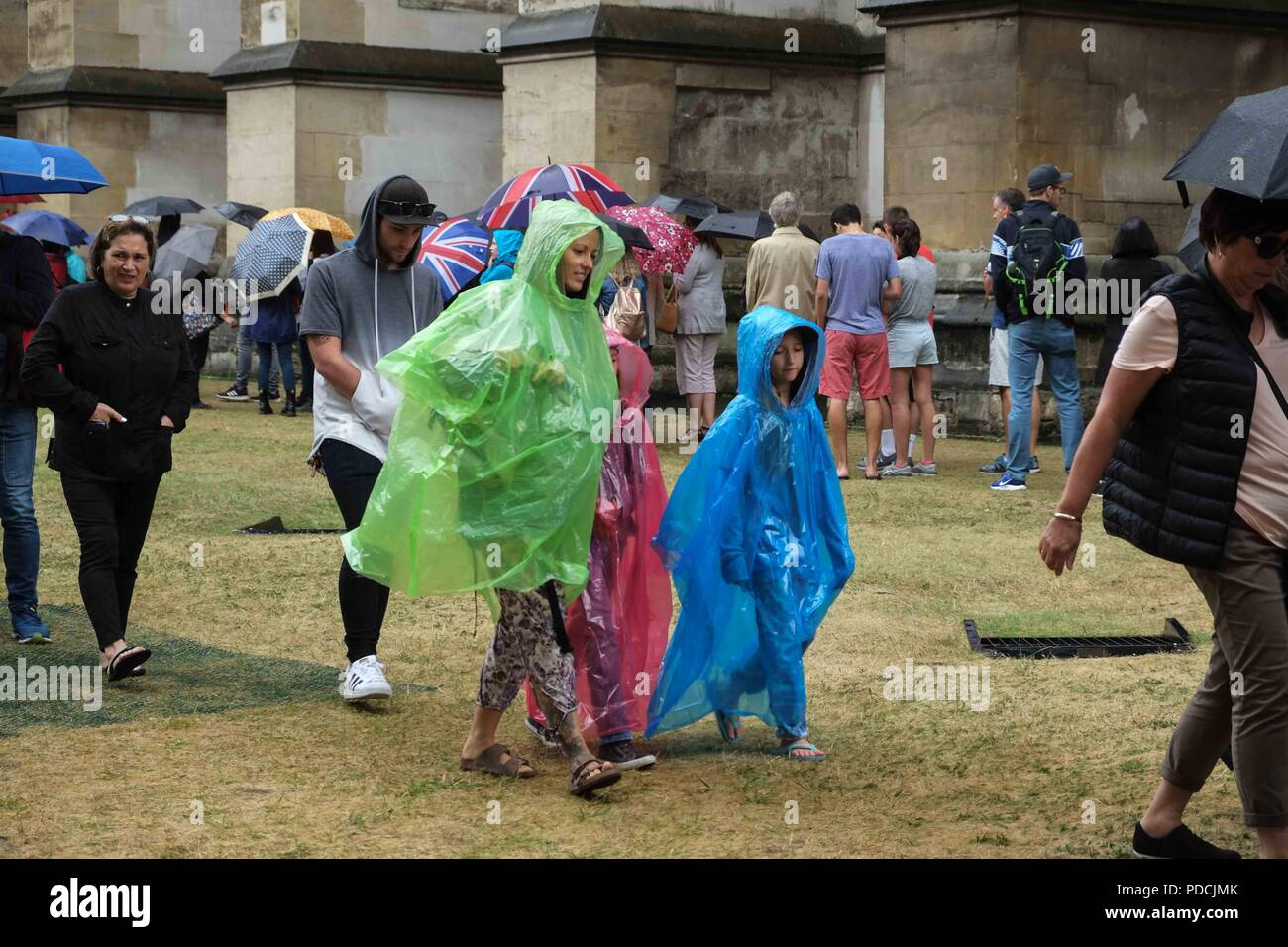 London 9th August 2018:  Visitors queue at Westminster Abbey in heavy rain . Credit: Claire Doherty/Alamy Live News - Stock Image