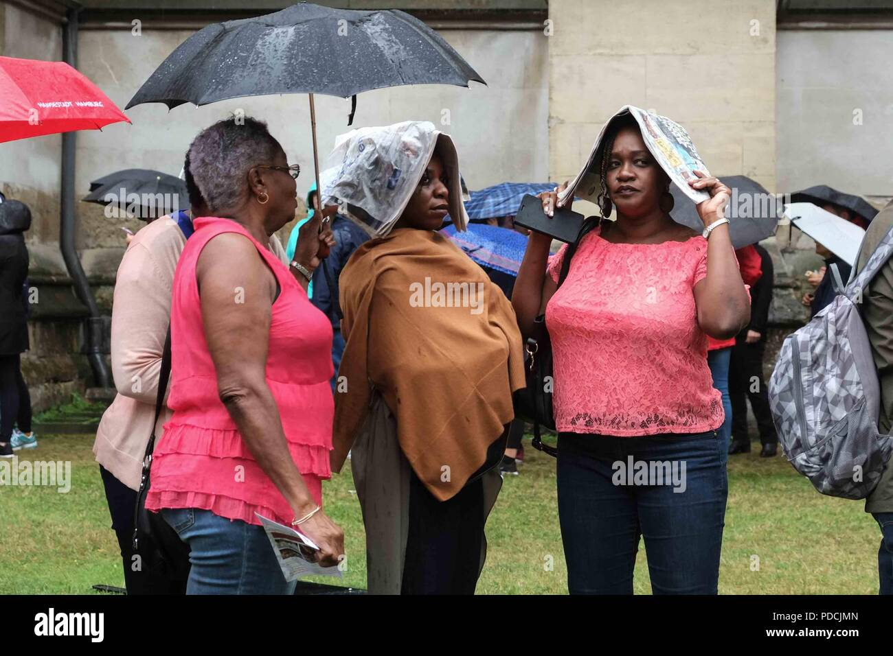 London 9th August 2018:  Two women shelter from the rain with newspapers covering their heads at Westminster Abbey. Credit: Claire Doherty/Alamy Live News - Stock Image
